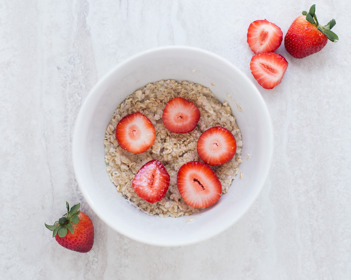 bowl of oatmeal and strawberries on a white table