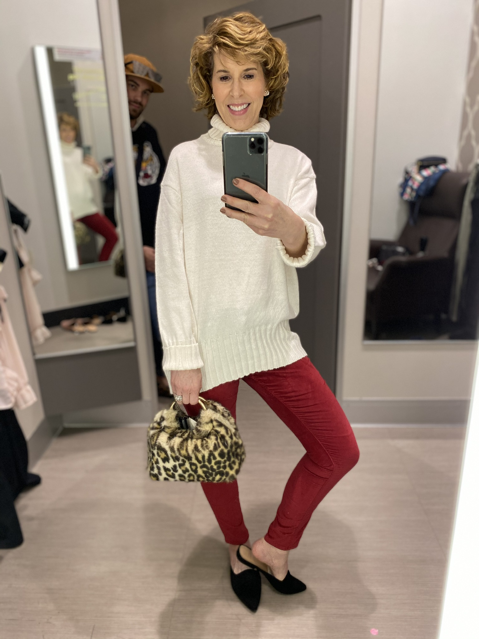 dressing room selfie of woman in red velvet jeans and cream turtleneck with animal print purse