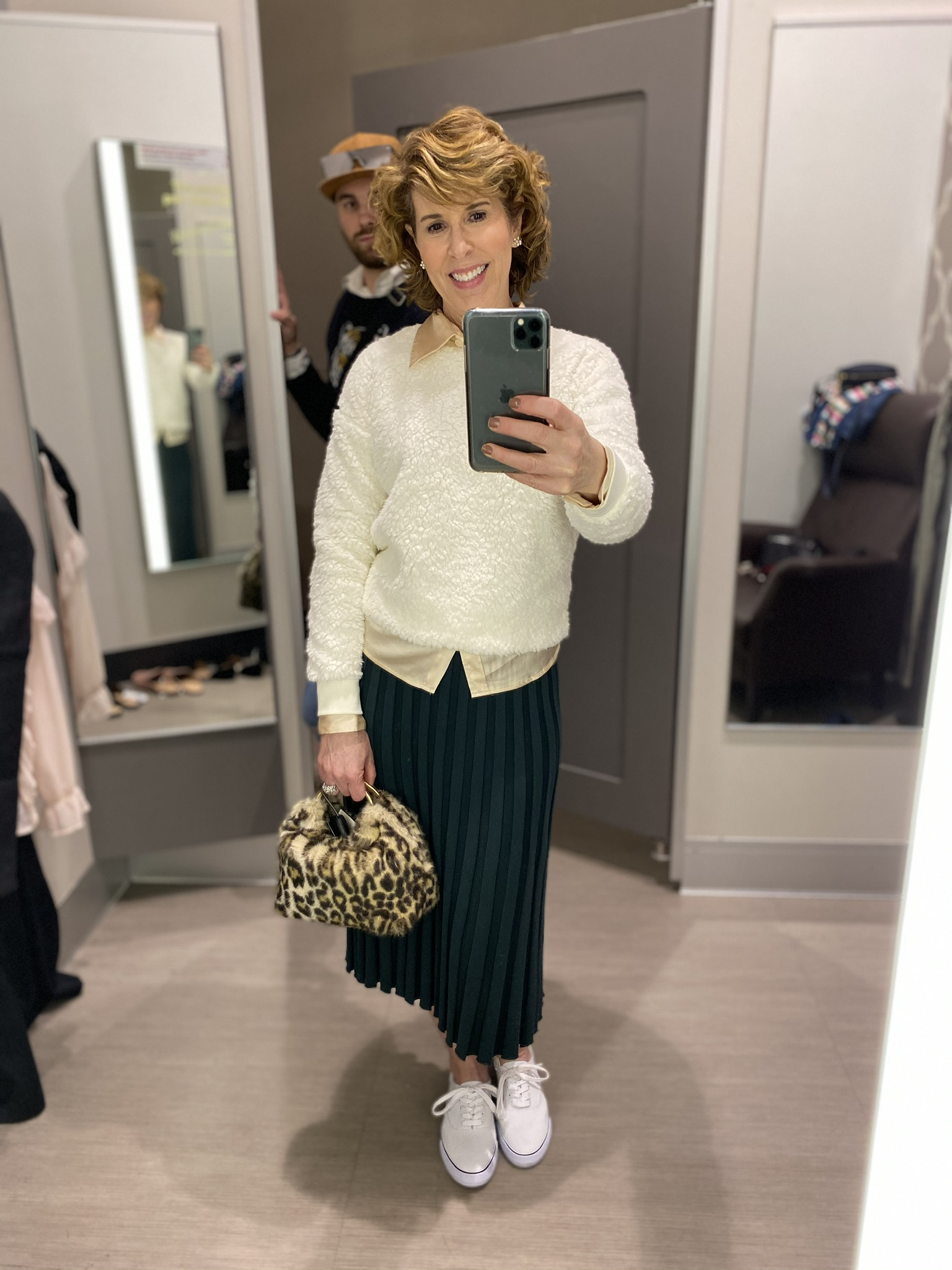 dressing room selfie of woman in green pleated skirt, cream sweater with blush button down under and leopard bag