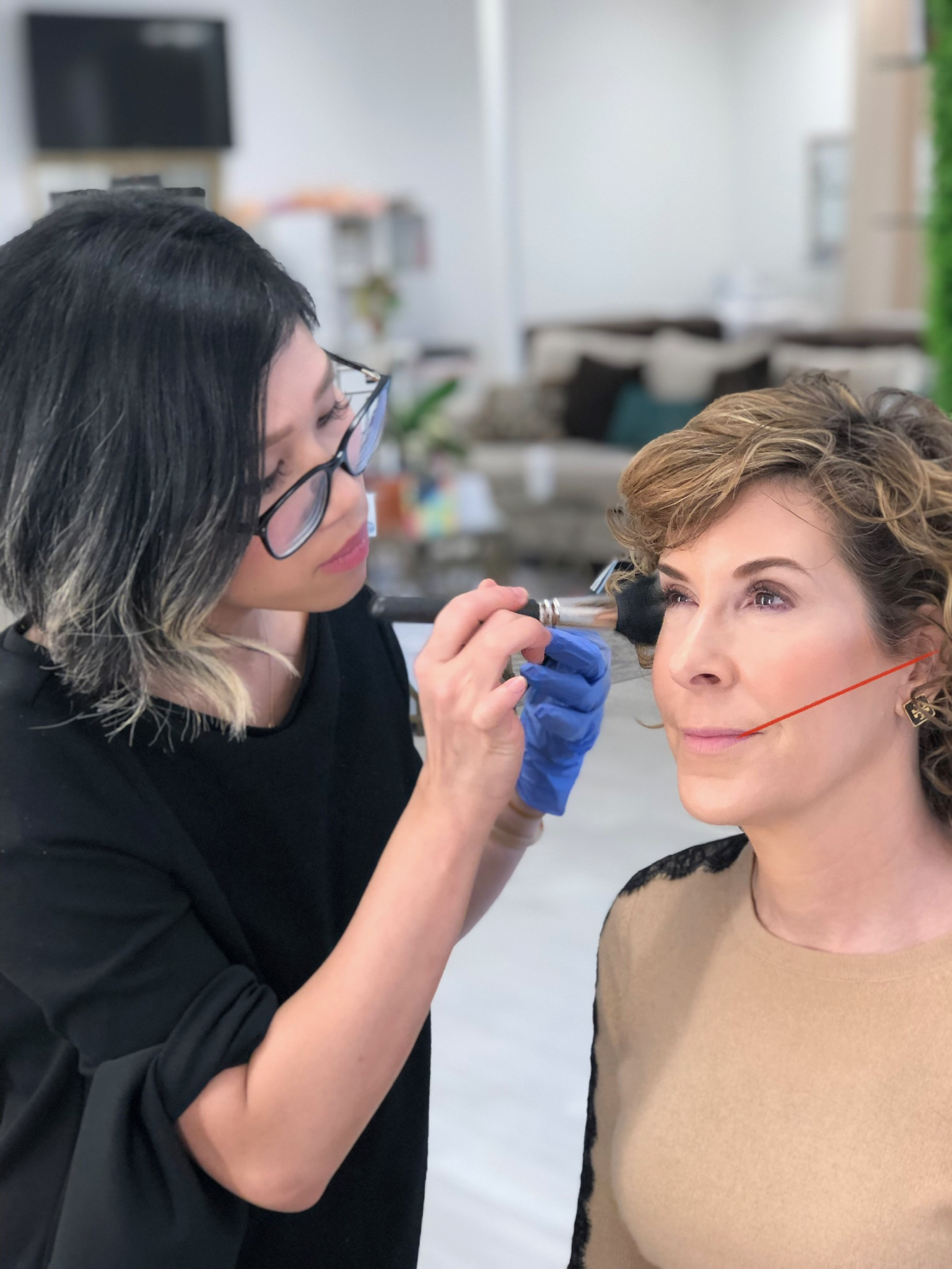 woman getting makeup done with red line on her face to show where to contour cheekbones