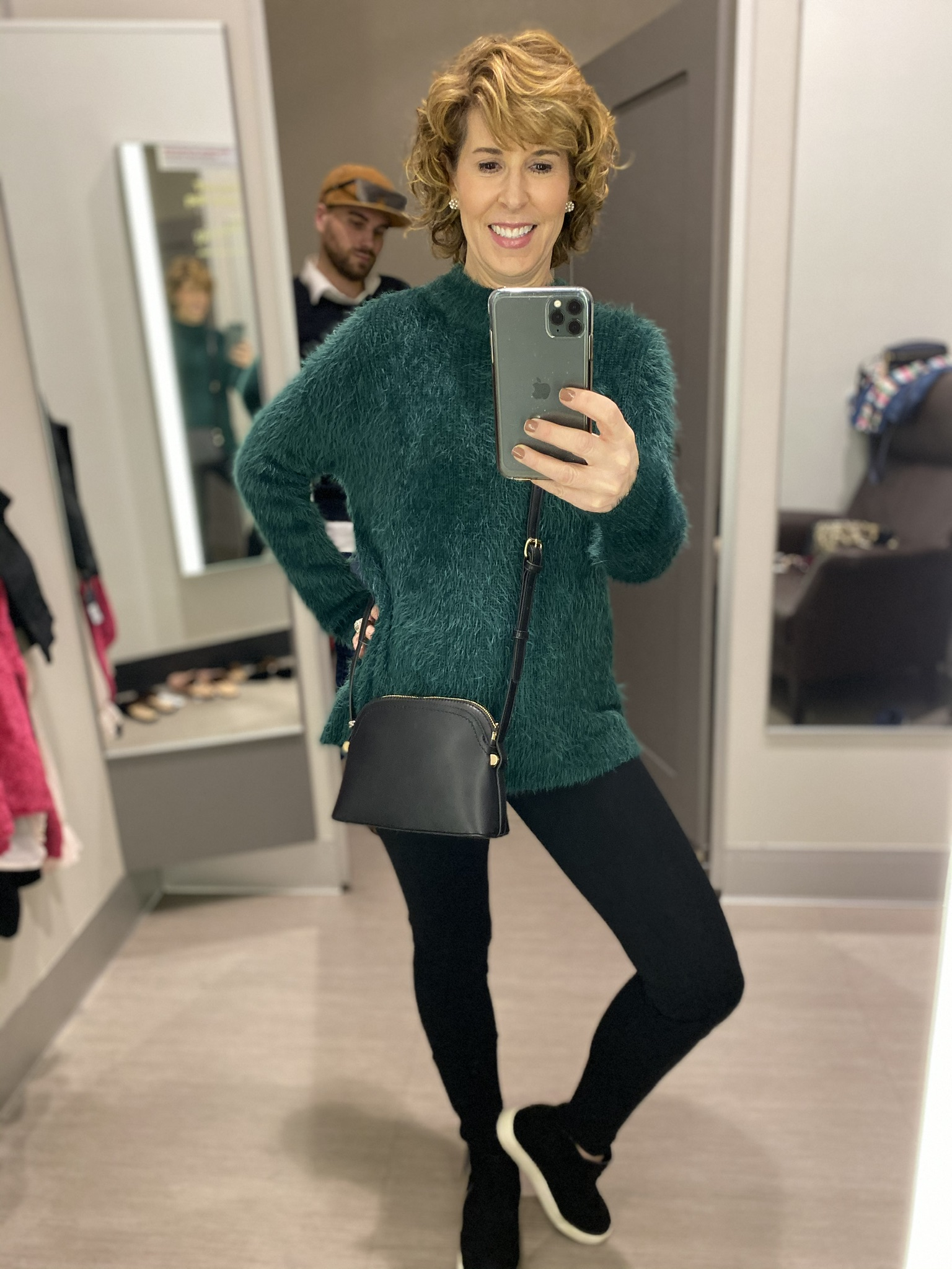 dressing room selfie of woman in long green fuzzy sweater, black leggings and black sneakers