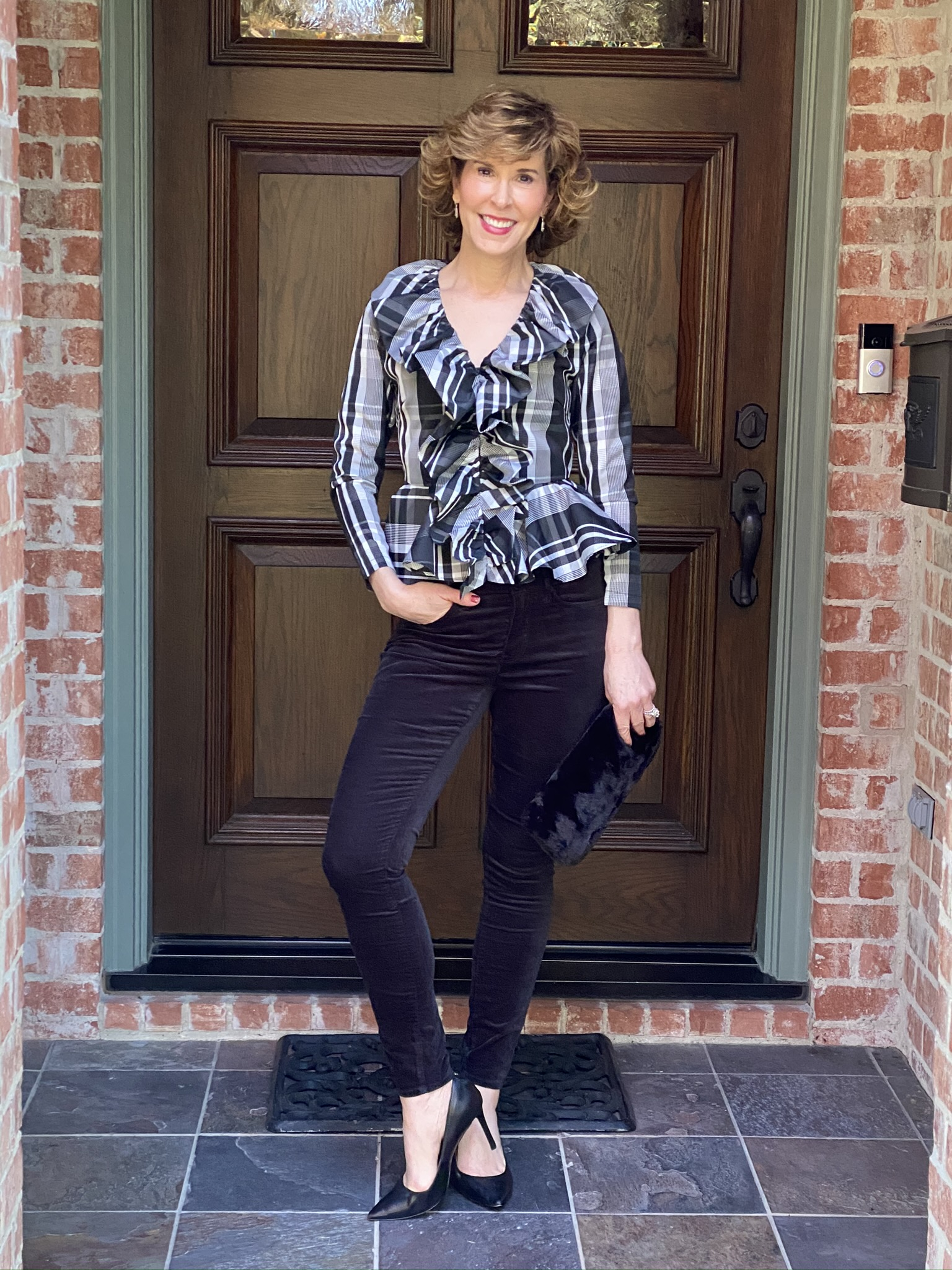 woman standing by front door in black and white plaid ruffled top with black velvet jeans holiday party look