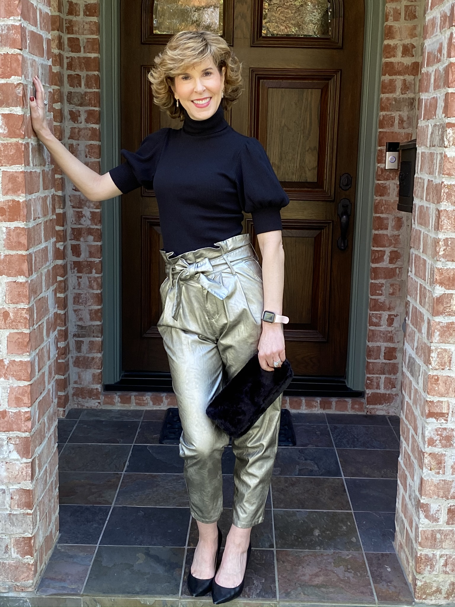 woman standing by front door in metallic paper bag waist pants and short sleeve turtleneck holiday party look