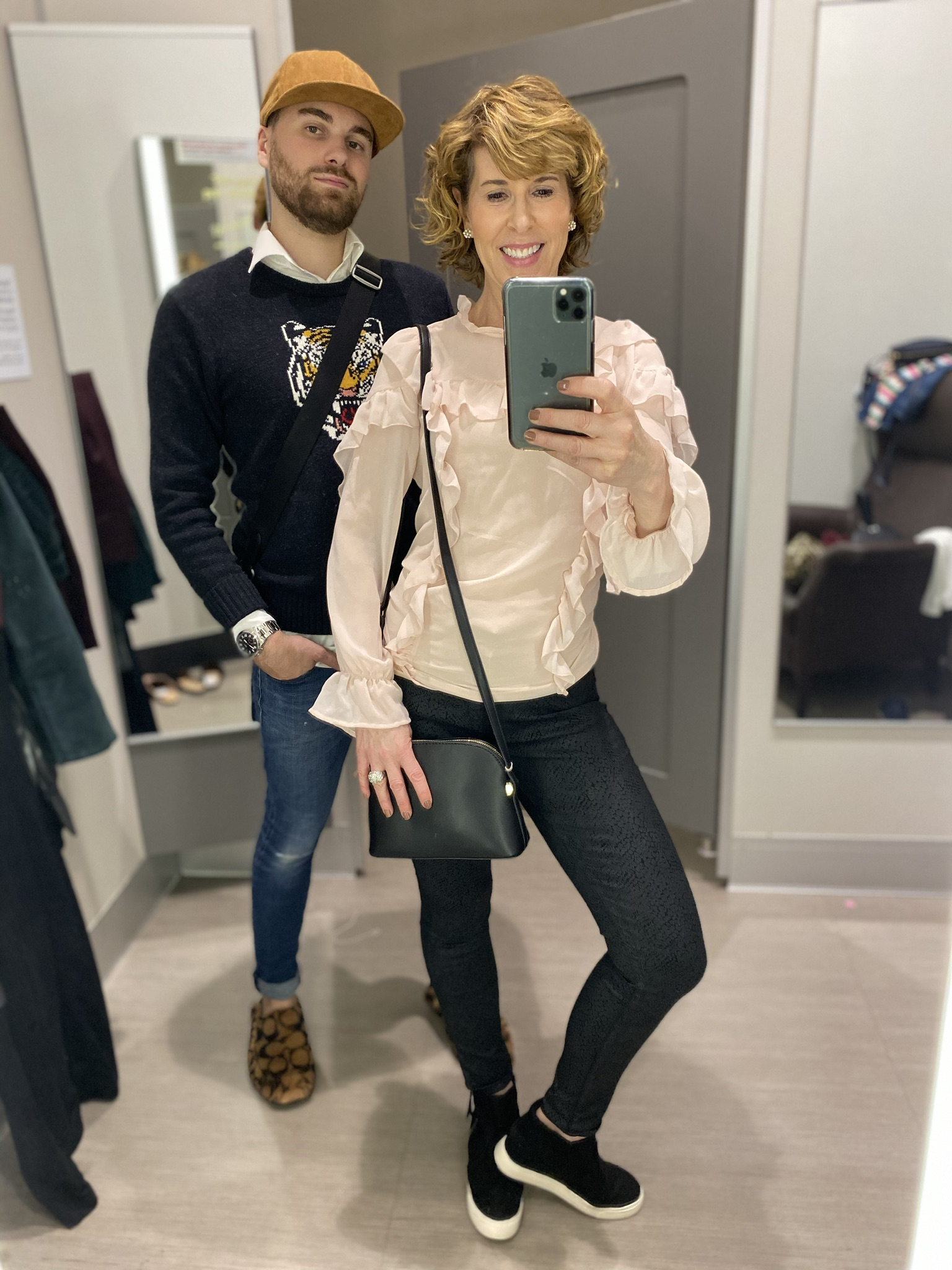 man with beard and woman in pink ruffled top and jeans taking dressing room selfie