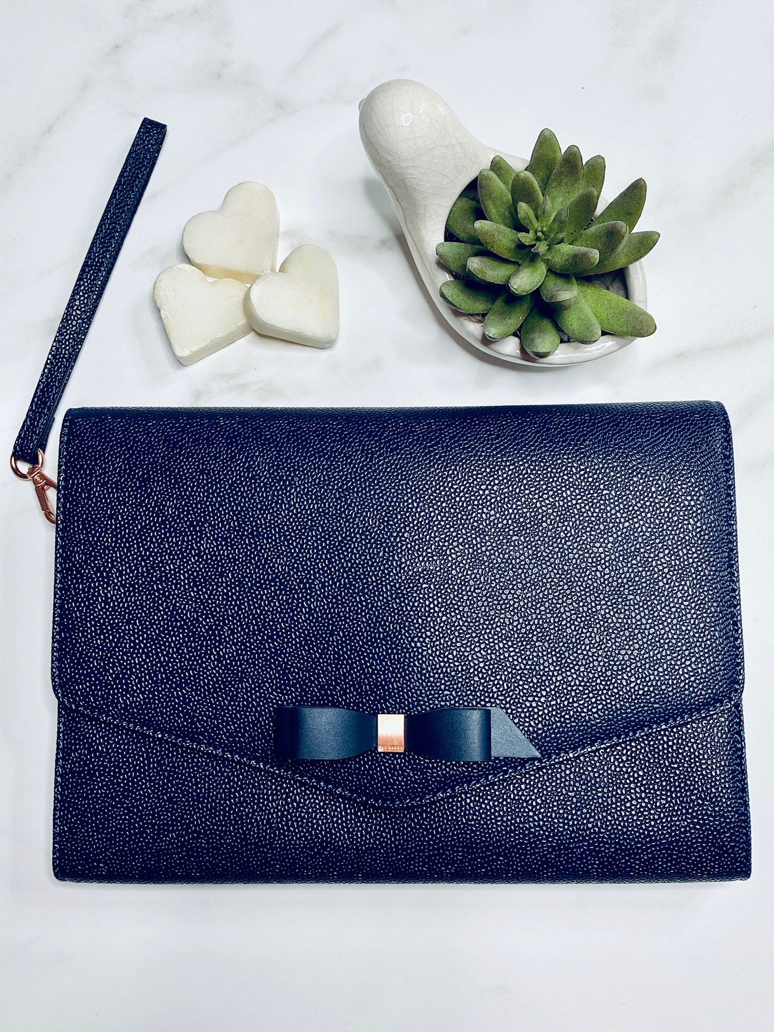 navy blue clutch on white background with plant and heart soaps