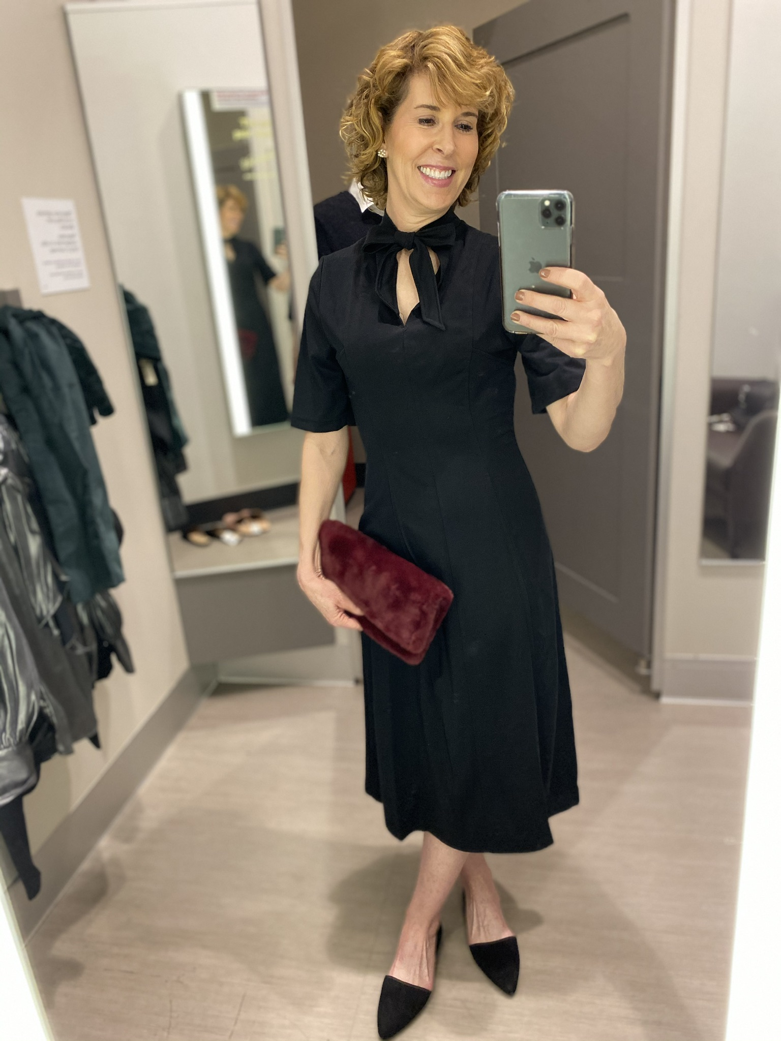 dressing room selfie of woman in black dress with bow at neckline