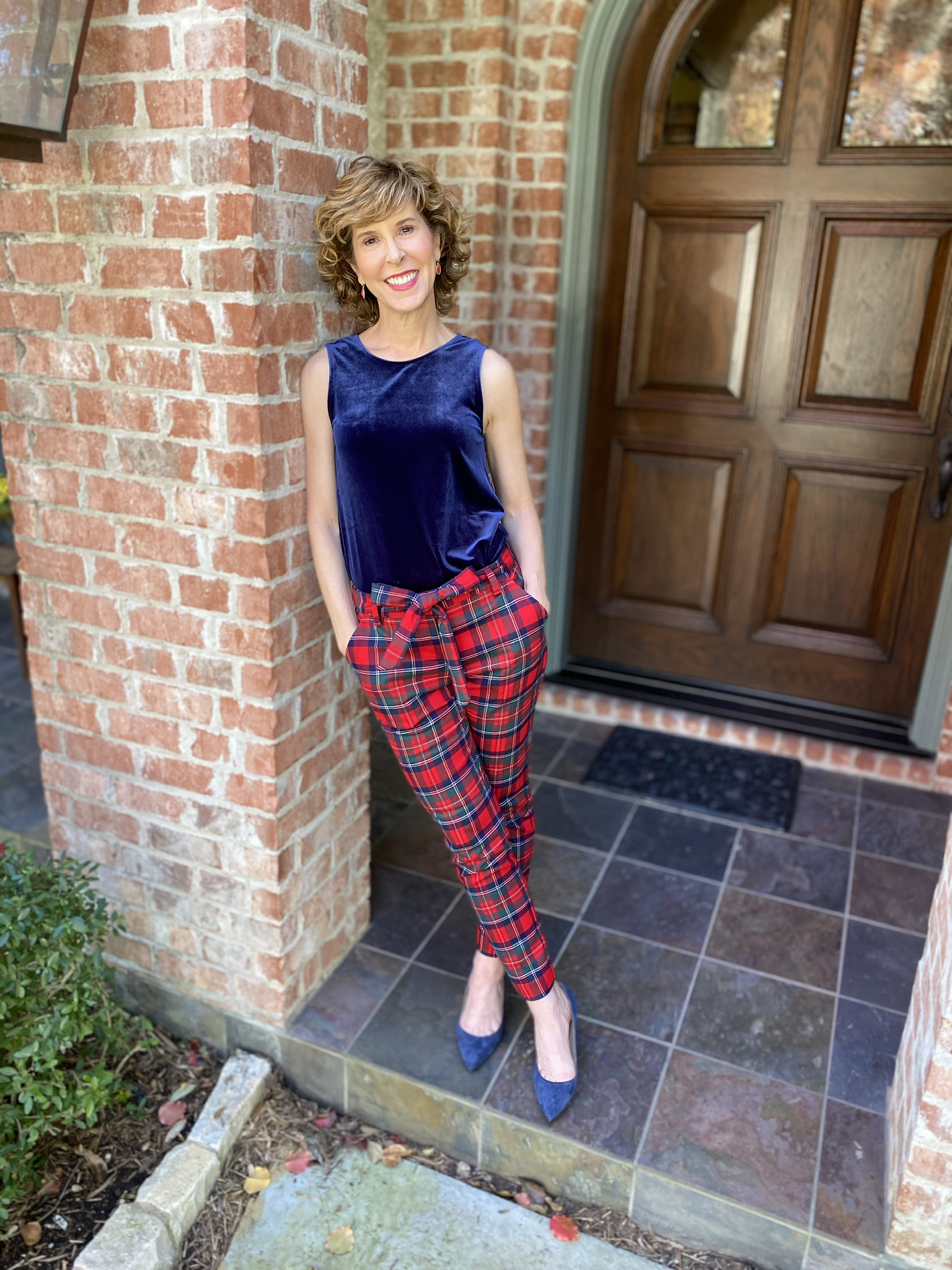 woman standing by front door wearing navy velvet tank and holiday plaid pants holiday party look