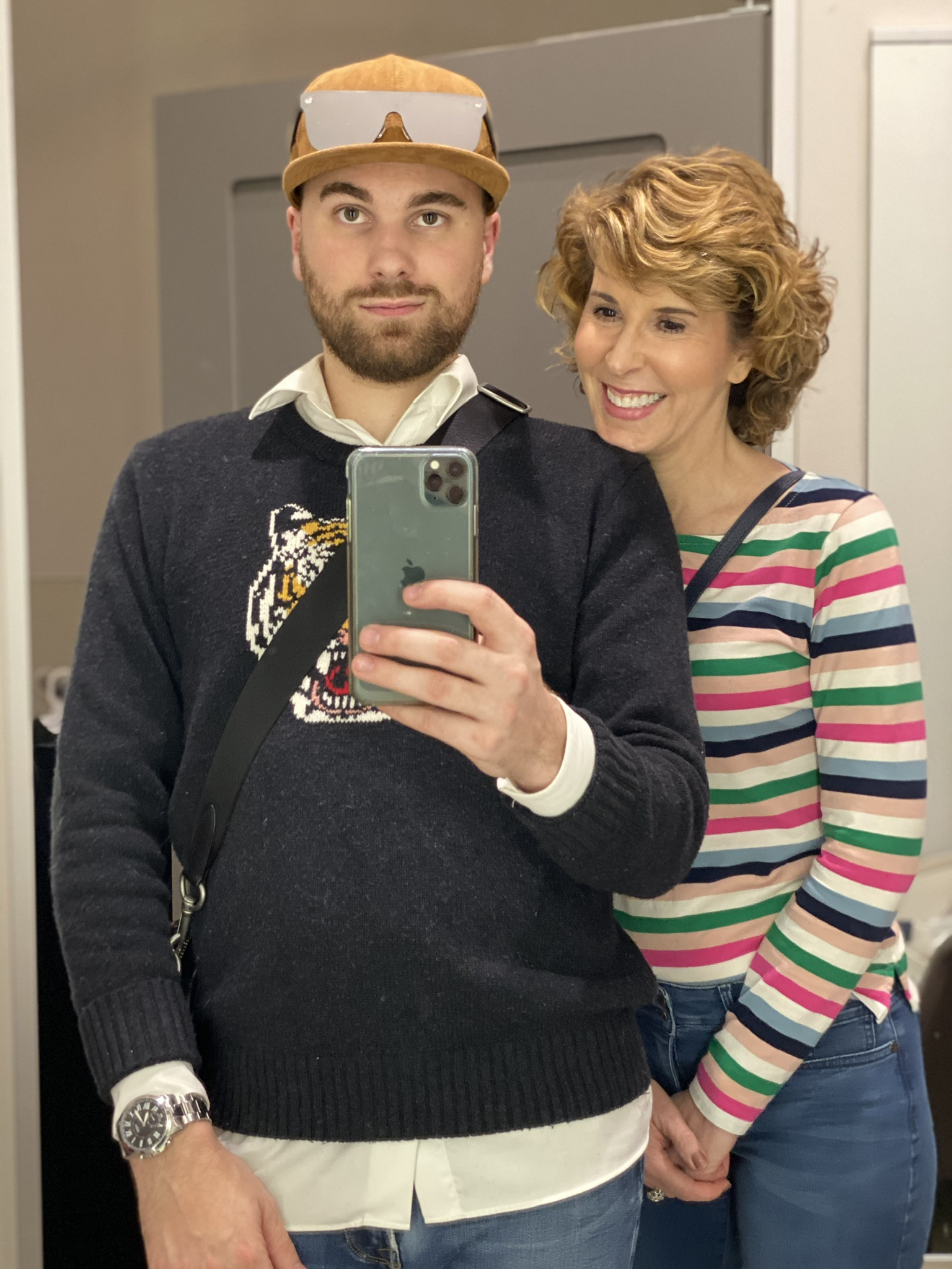 man with beard and woman in striped shirt taking mirror selfie