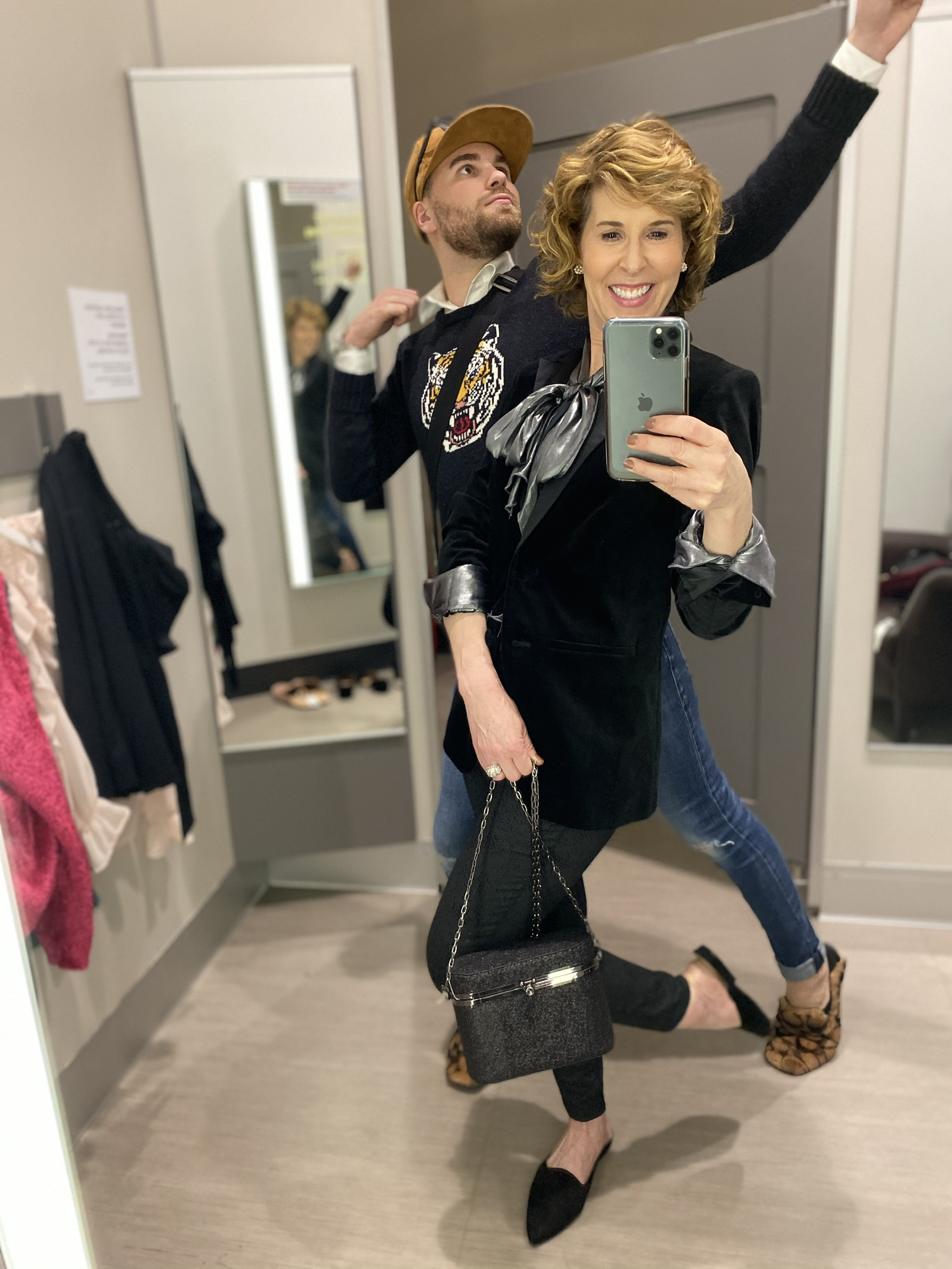 dressing room selfie of woman in metallic tie neck top, velvet jacket and green jeans