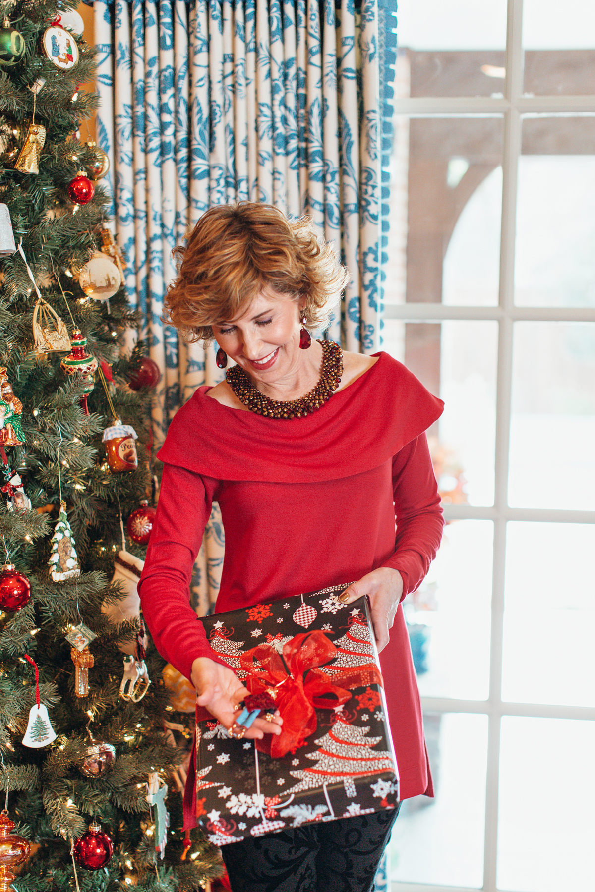 woman wearing red top holding a christmas gift and standing in front of a tree looking at one of her gift giving traditions of attaching an ornament to the exterior of a gift