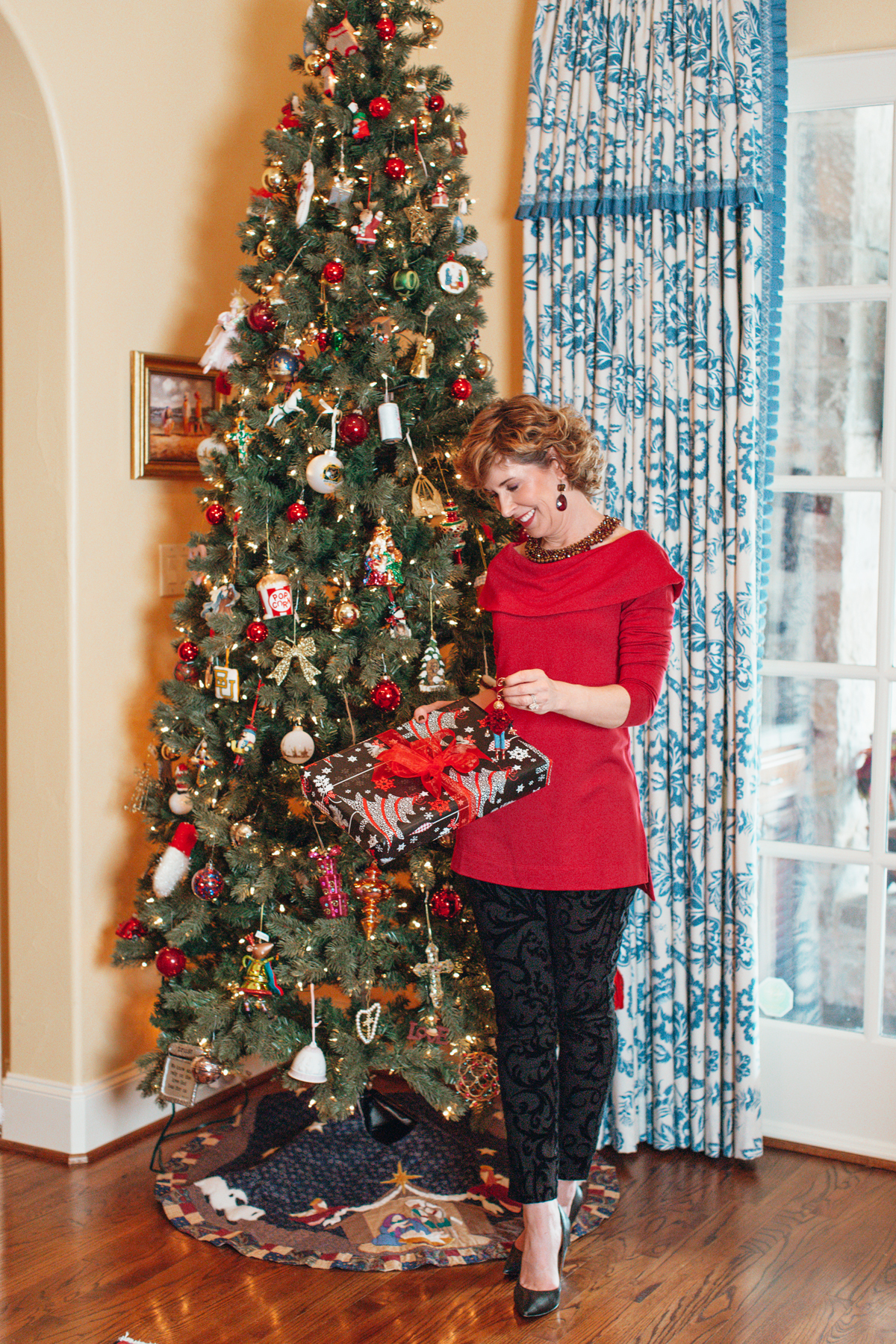 woman wearing red top and black pants holding a gift in front of a christmas tree and showing her family's gift giving traditions