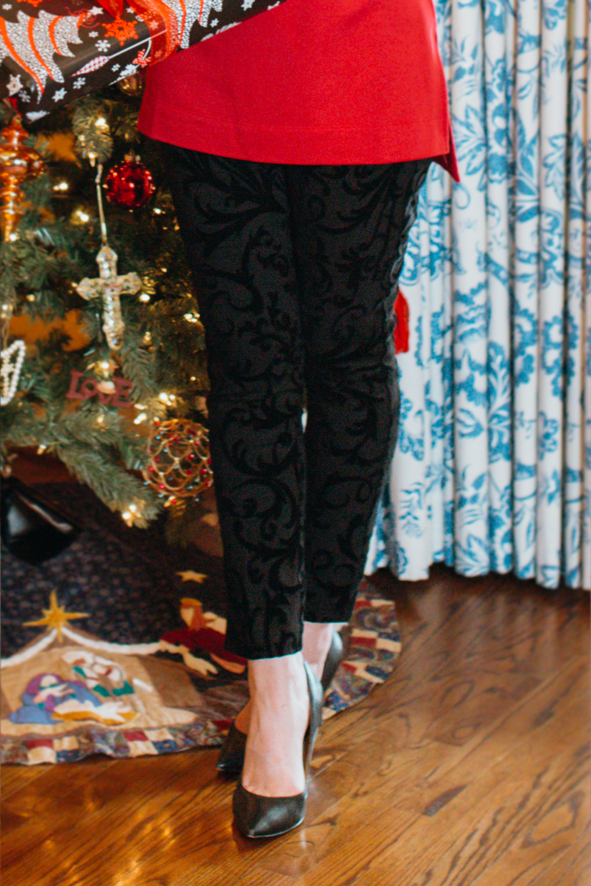 woman's black scroll pants from chico's standing in front of a christmas tree