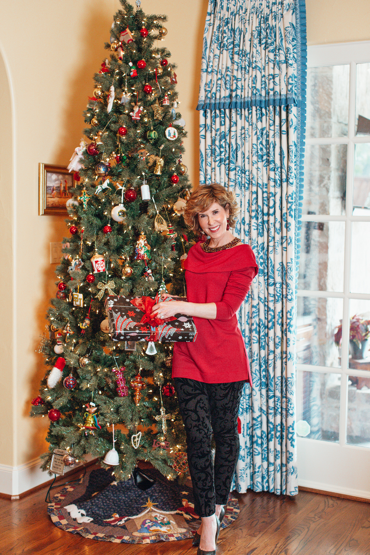 woman dressed in red top and black pants from chico's standing in front of a christmas tree talking about gift giving traditions