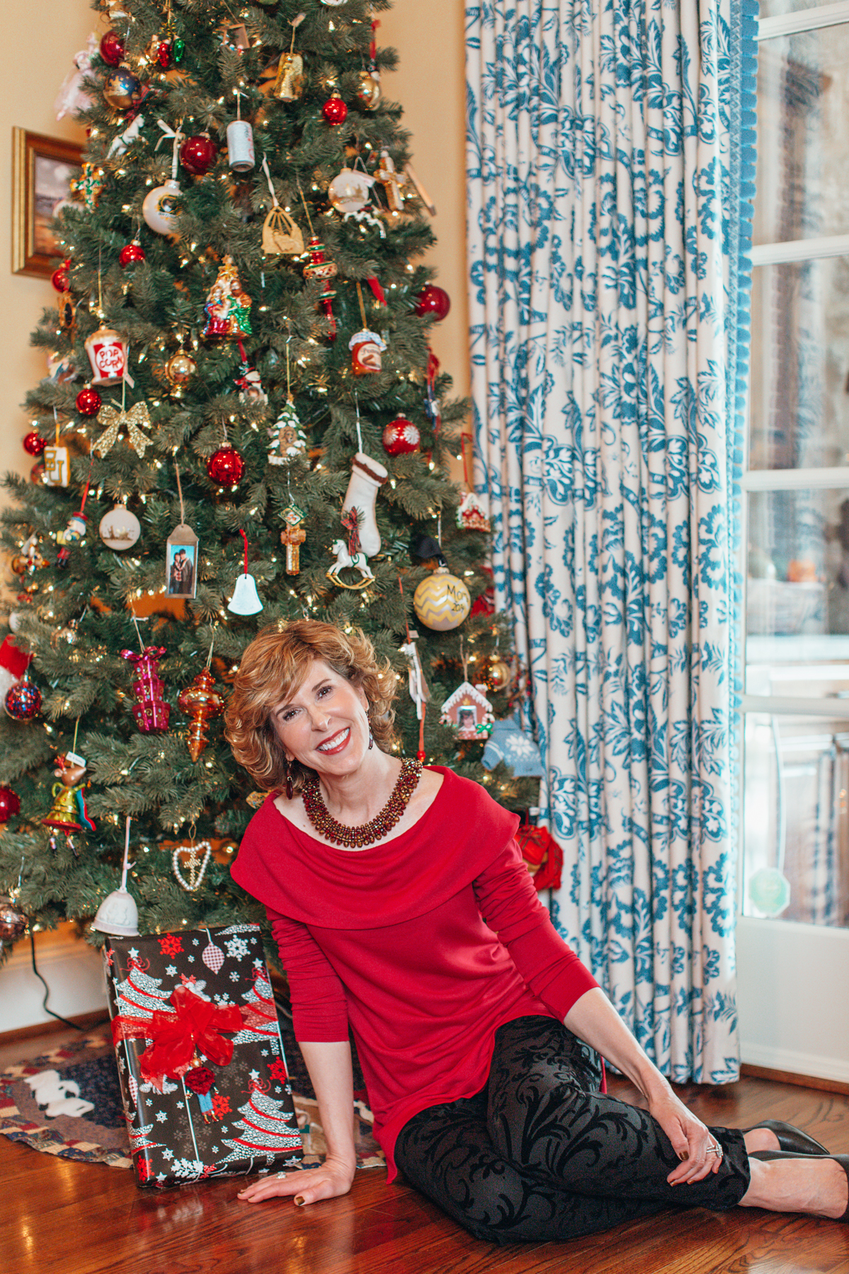 woman dressed in red top and black pants from chico's sitting in front of a christmas tree