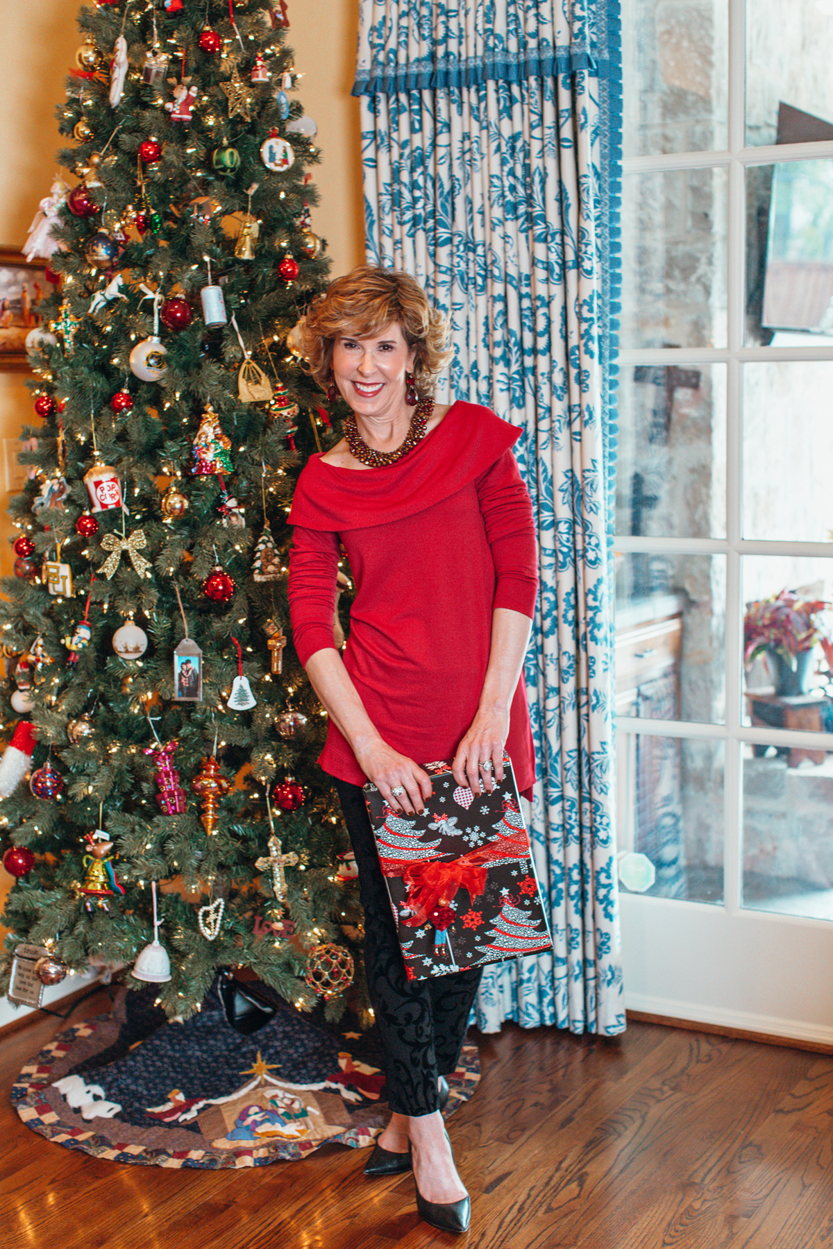 woman dressed in red top and black pants from chico's standing in front of a christmas tree