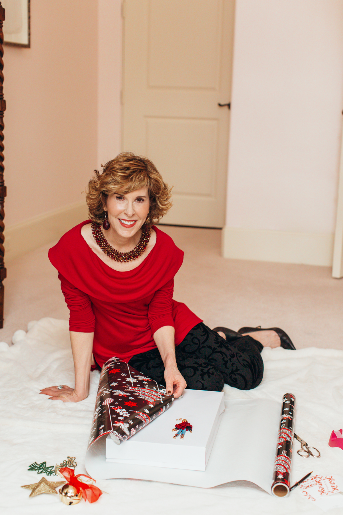 woman sitting on floor wearing red top and black pants from chicos wrapping a gift