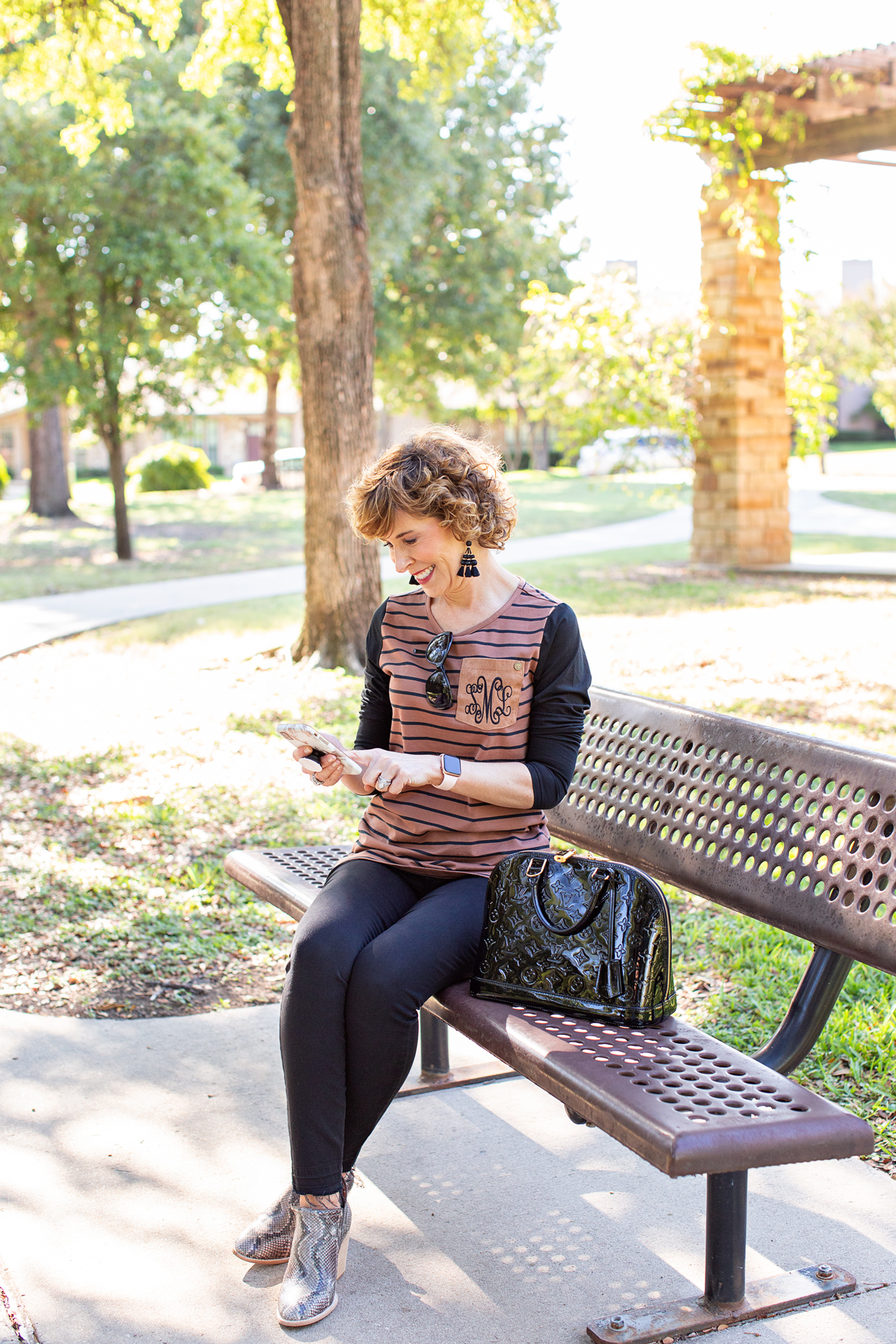 woman dressed in brown and black striped shirt sitting on a park bench looking at her phone