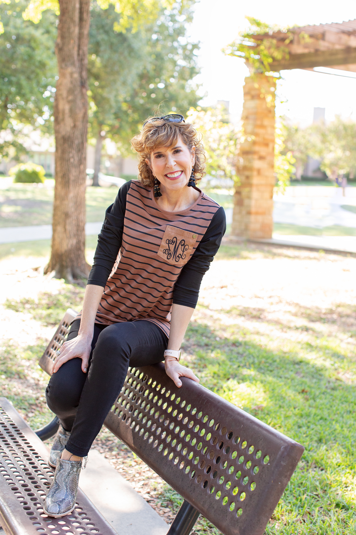 woman dressed in brown and black striped shirt sitting on the back of a park bench