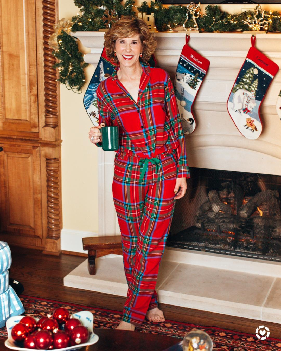 woman in holiday pajamas in front of a fireplace