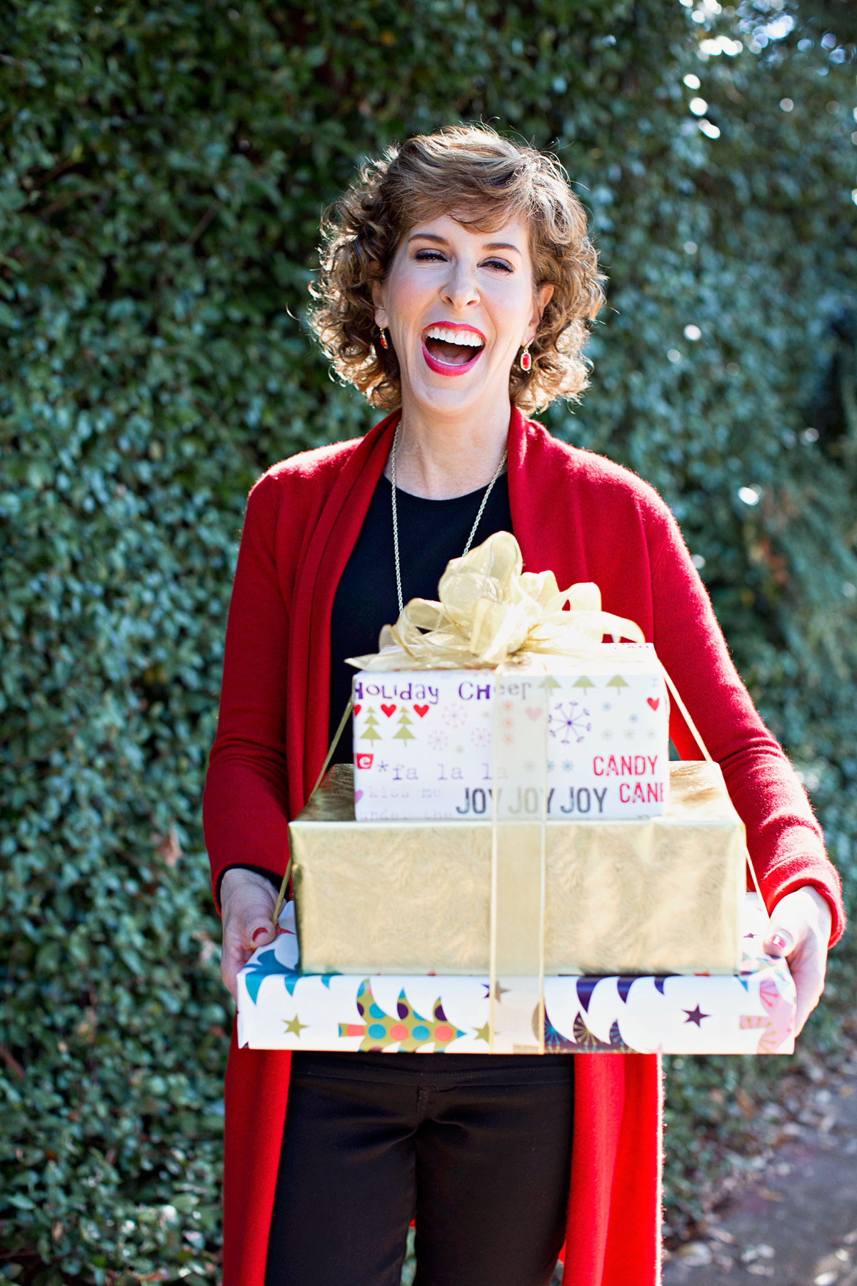 laughing woman holding three wrapped gifts