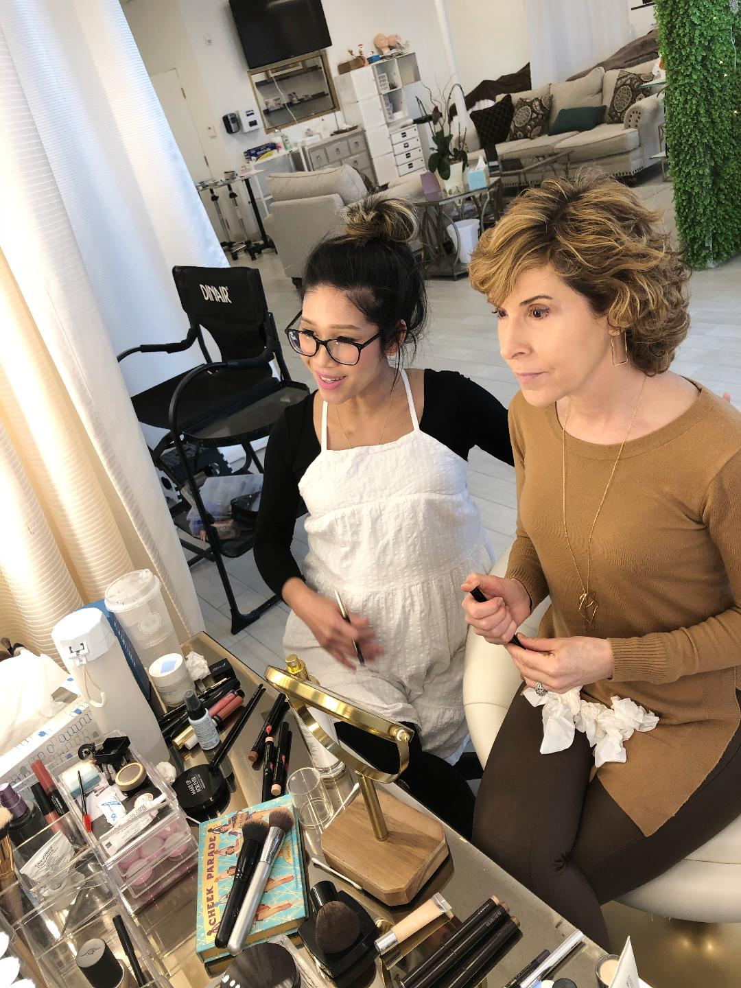 woman looking into makeup mirror during a makeup lesson