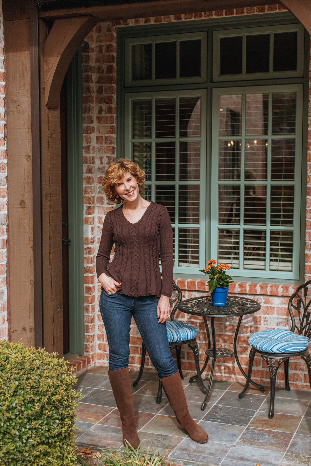 over 50 woman in brown sweater blue jeans and brown boots standing on a porch with a table and chairs in the background