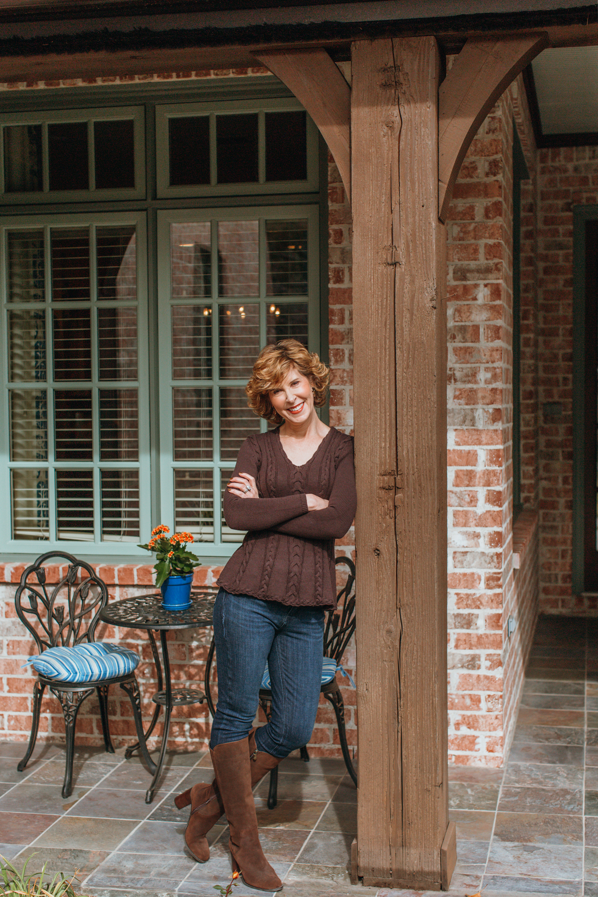 over 50 woman in brown sweater blue jeans and brown boots leaning against a pillar on a porch
