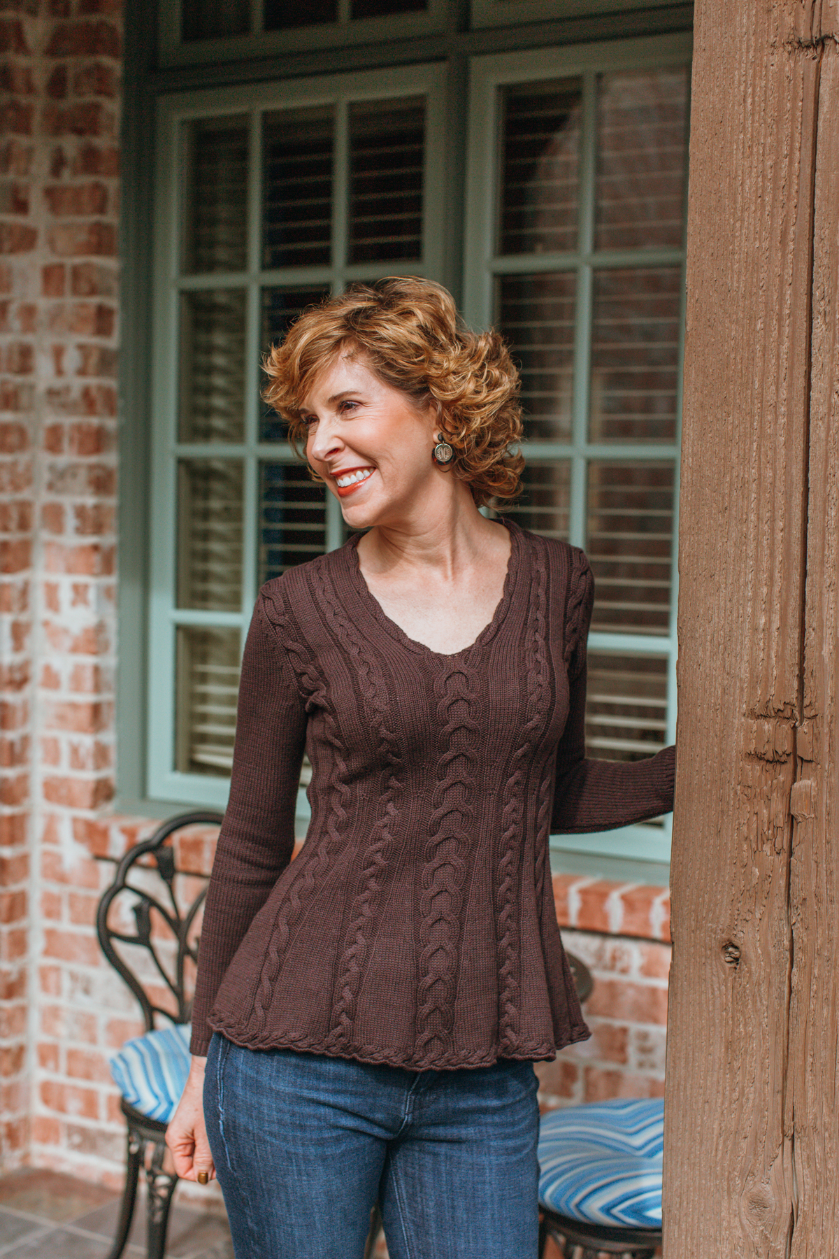 over 50 woman in brown sweater and blue jeans standing on a porch