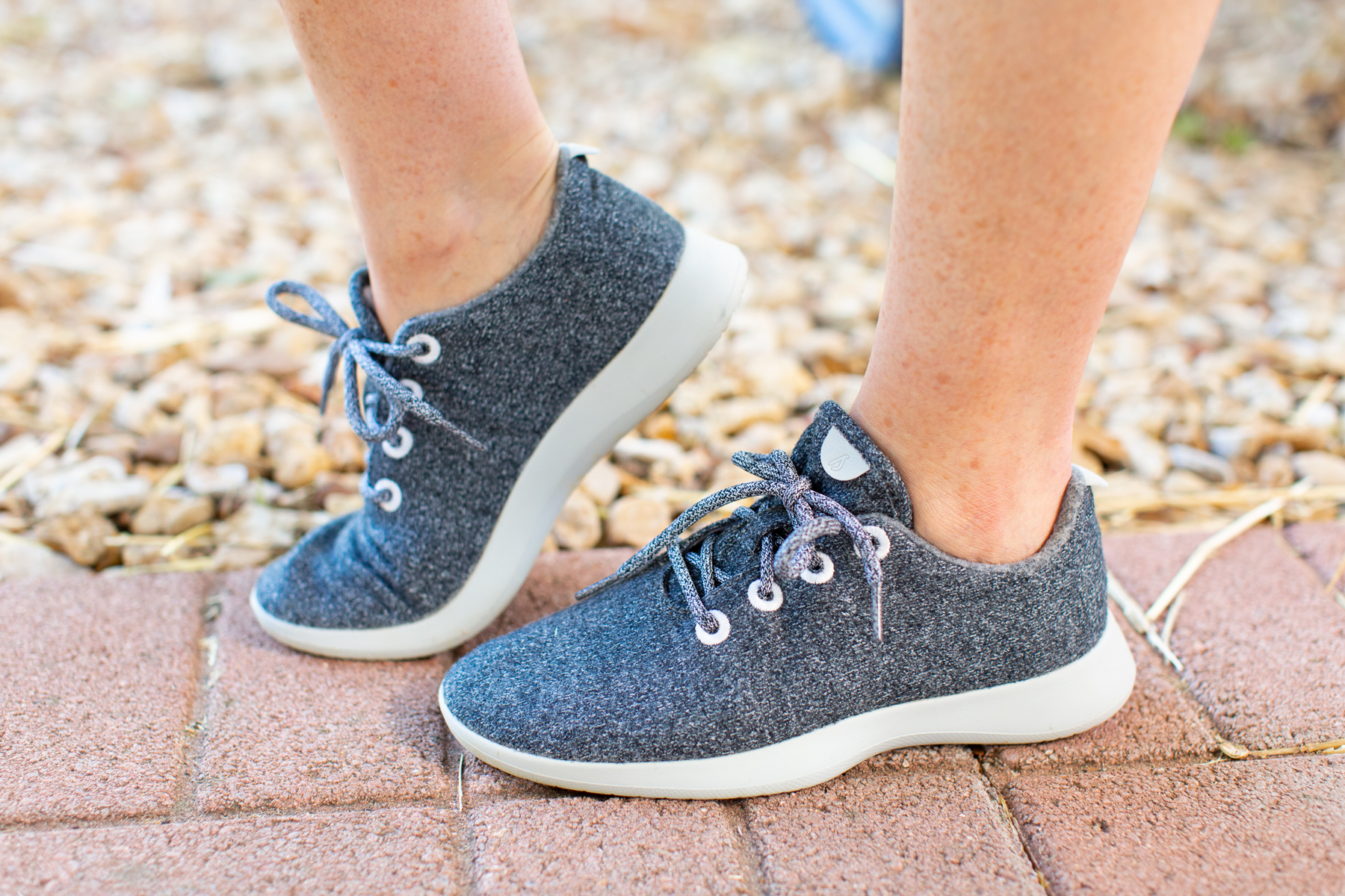womans feet wearing gray allbirds
