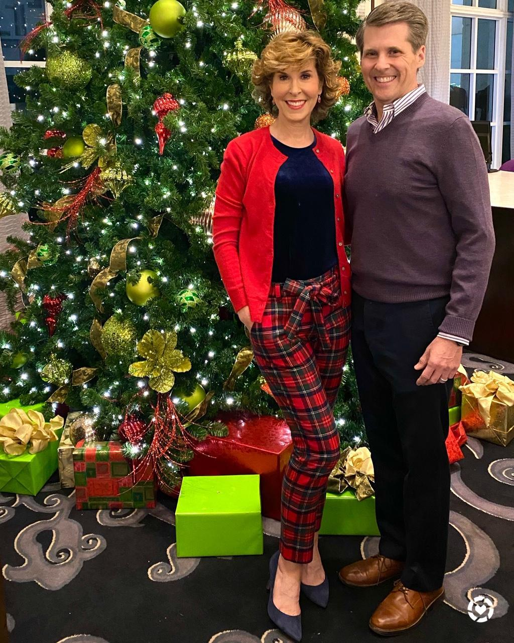 couple in holiday party attire standing in front of a christmas tree