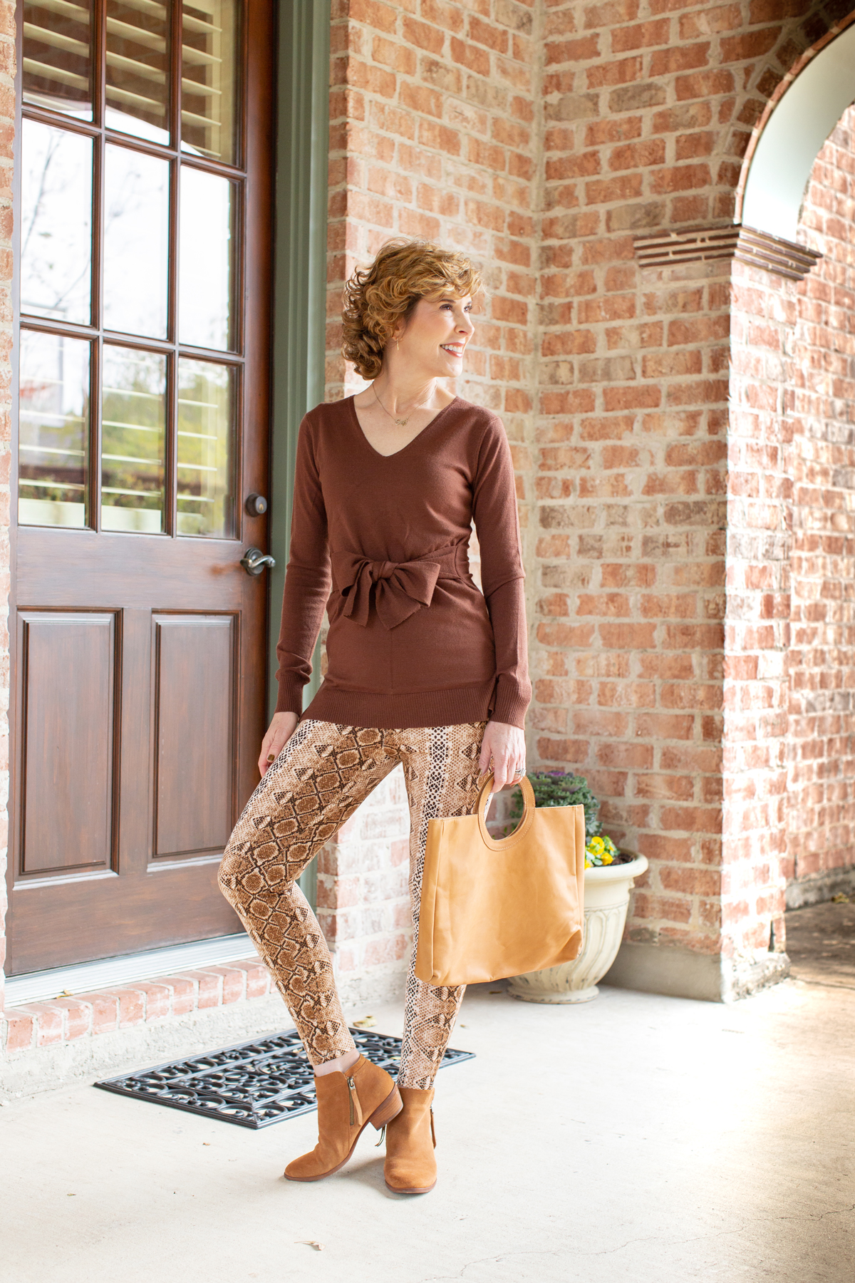 woman wearing a brown sweater and snakeprint leggings standing outside a house