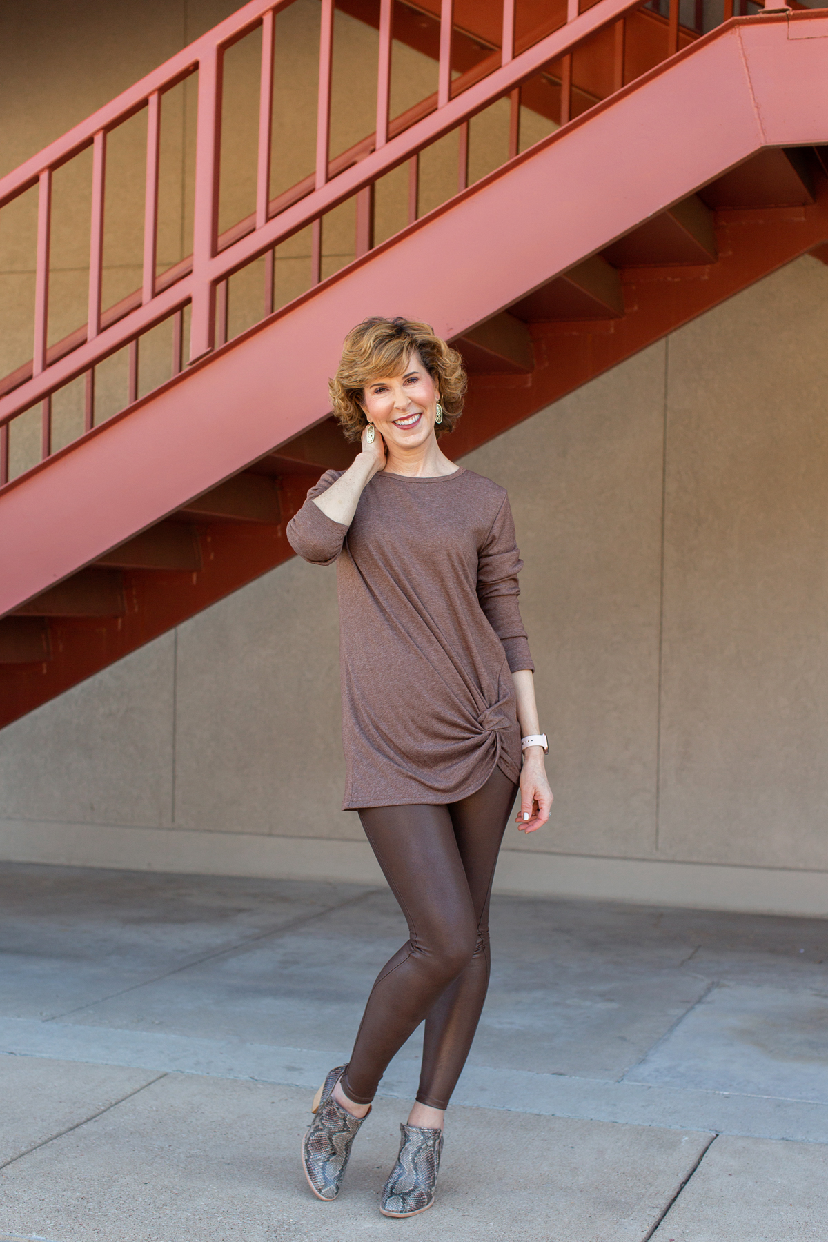 woman dressed in brown standing in front of a rust colored staircase