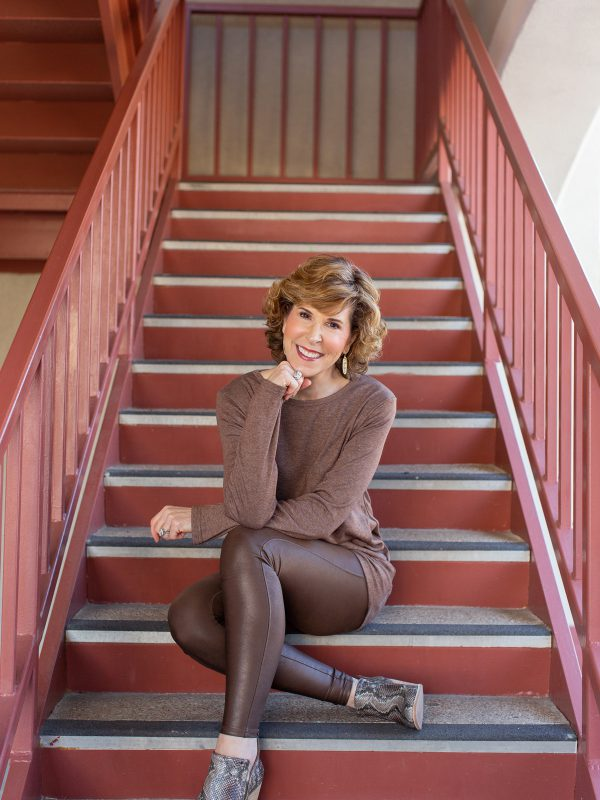 woman dressed in brown sitting on rust colored staircase