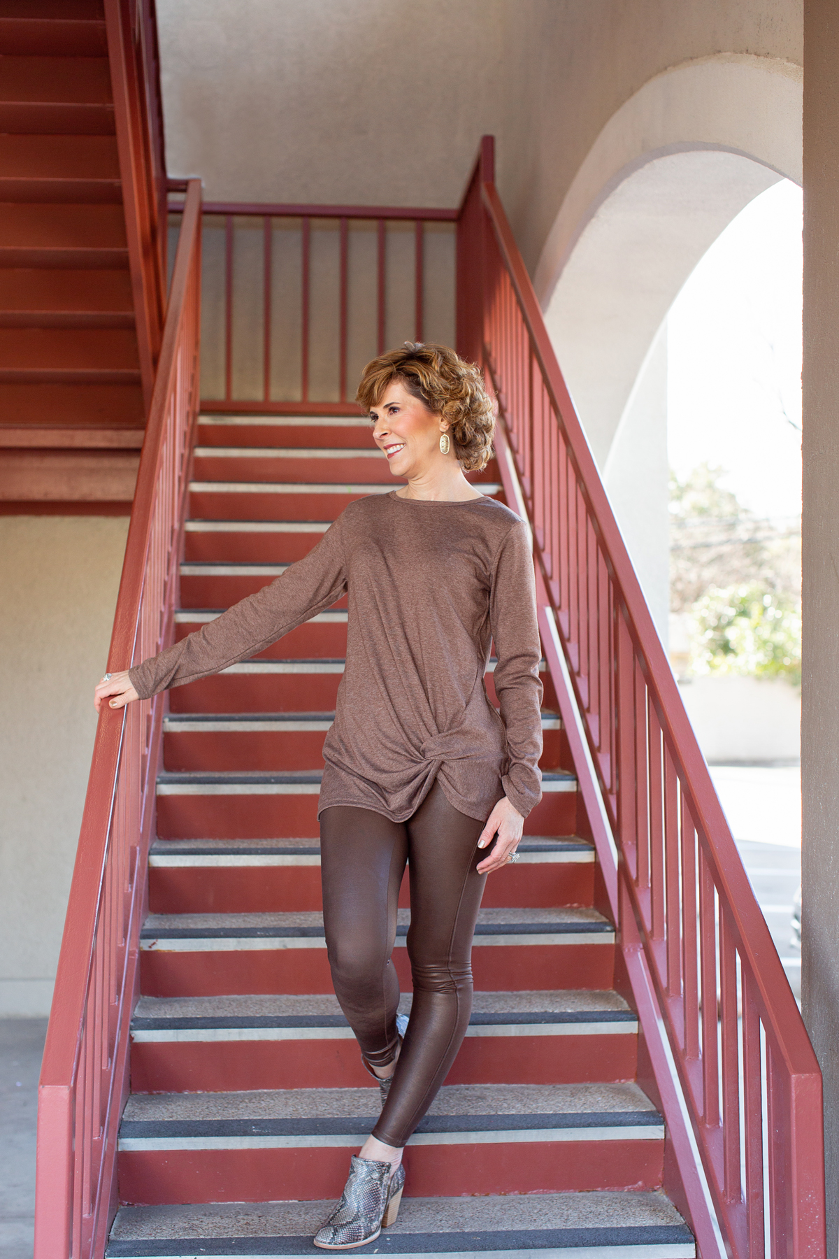 woman dressed in brown standing on rust colored staircase