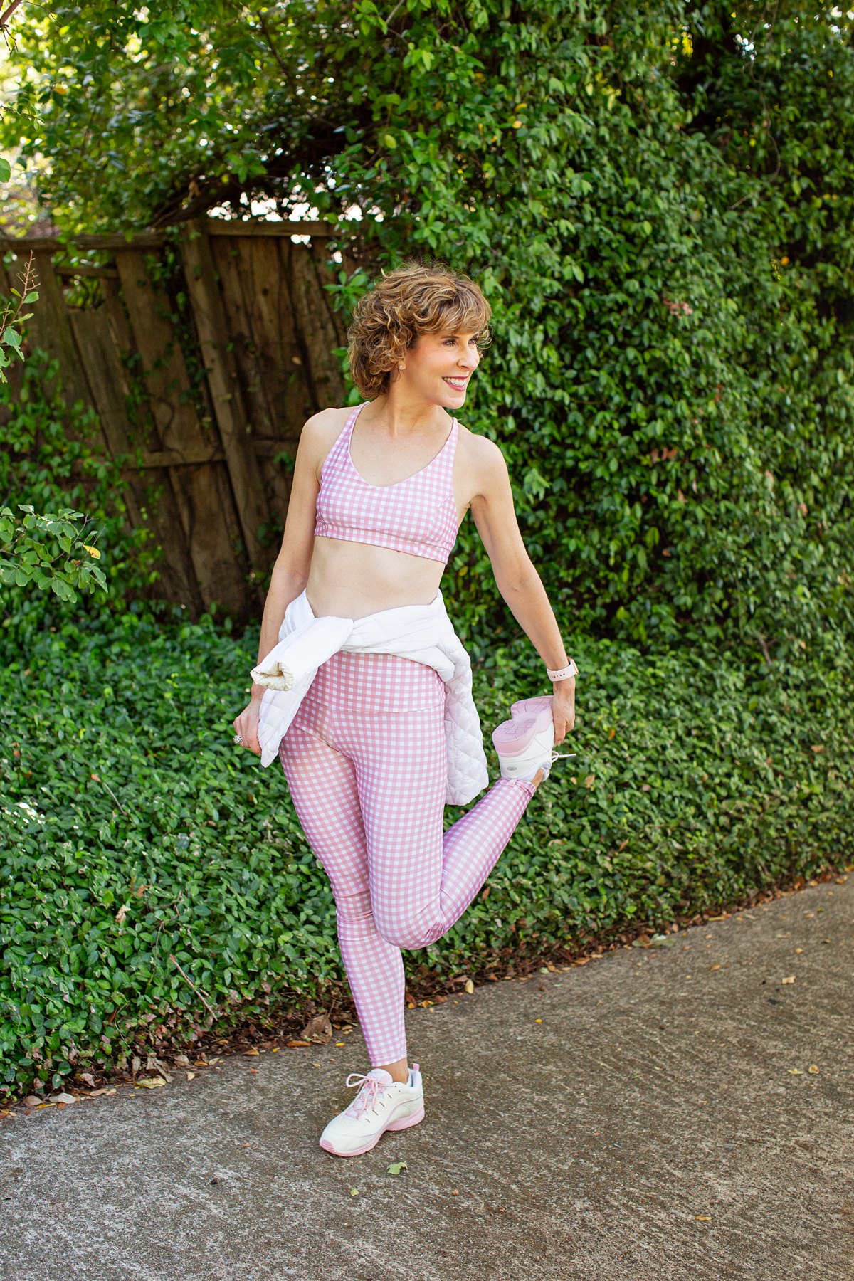 woman stretching in pink and white workout wear