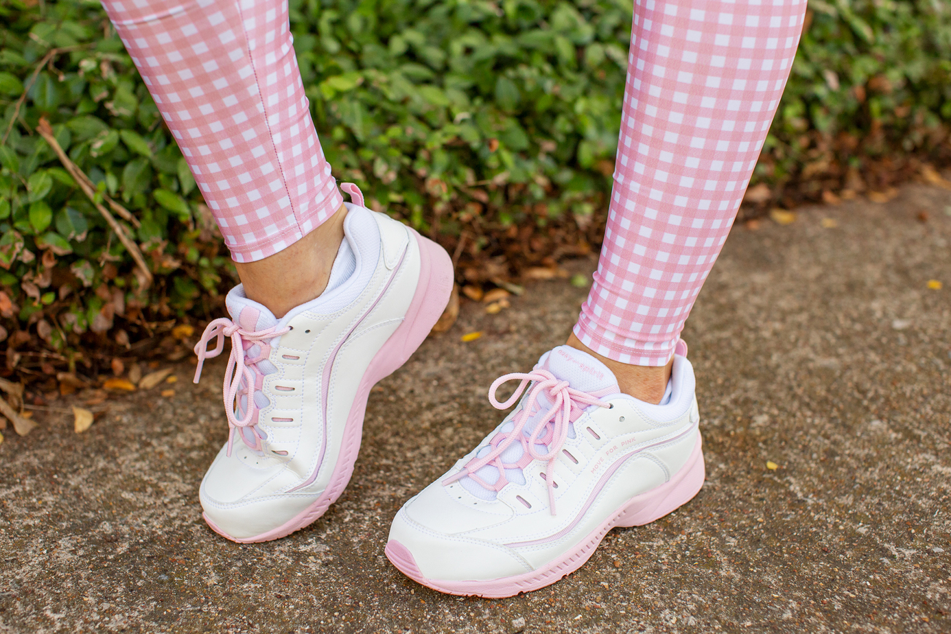 womans feet in pink and white easy spirit tennis shoes