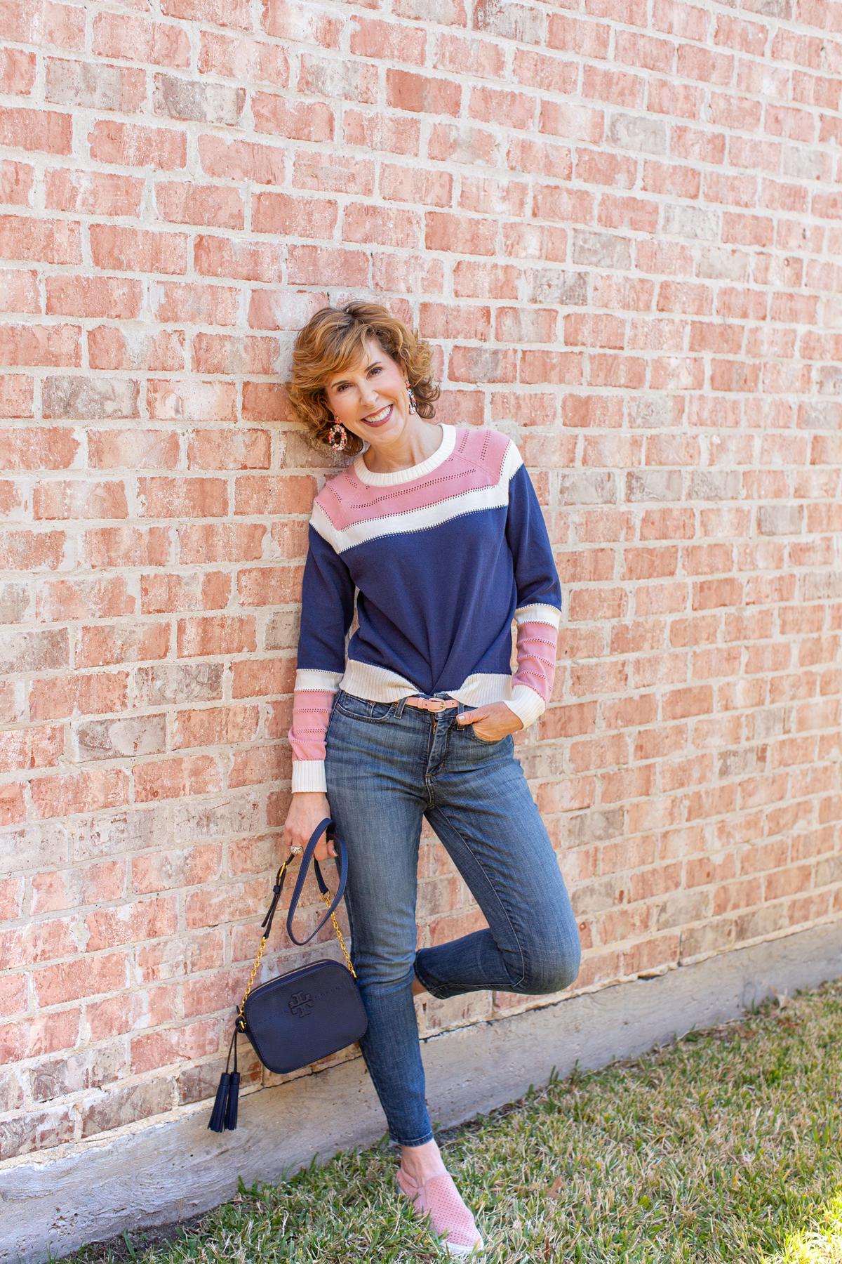 woman wearing pink and navy sweater and jeans leaning against a pink brick wall