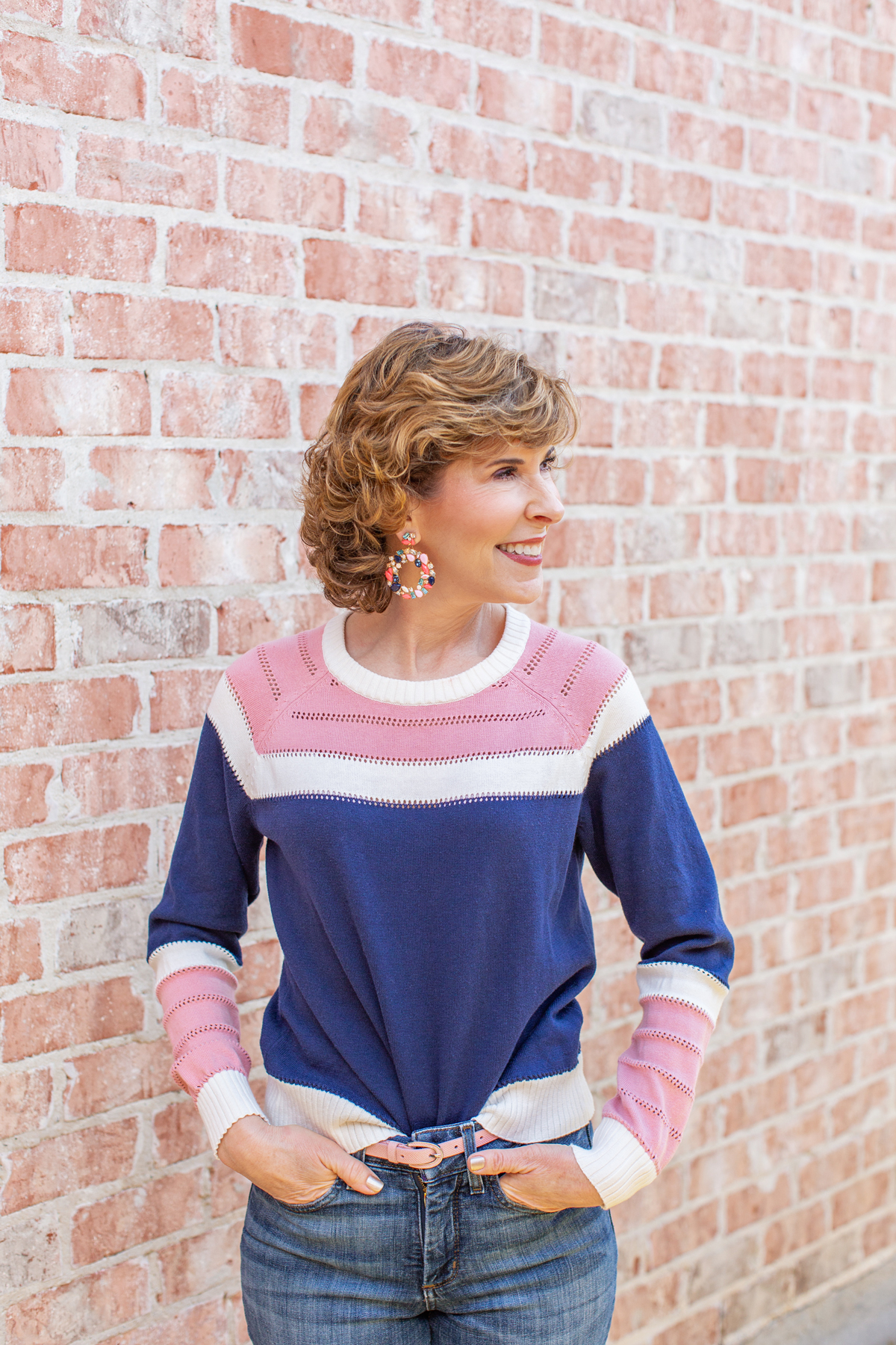 woman wearing pink and navy sweater and jeans with big earrings looking to the side