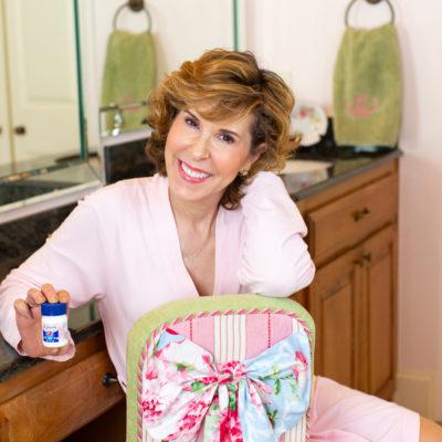 woman wearing pink bathrobe sitting on a vanity chair backwards holding st joseph aspirin