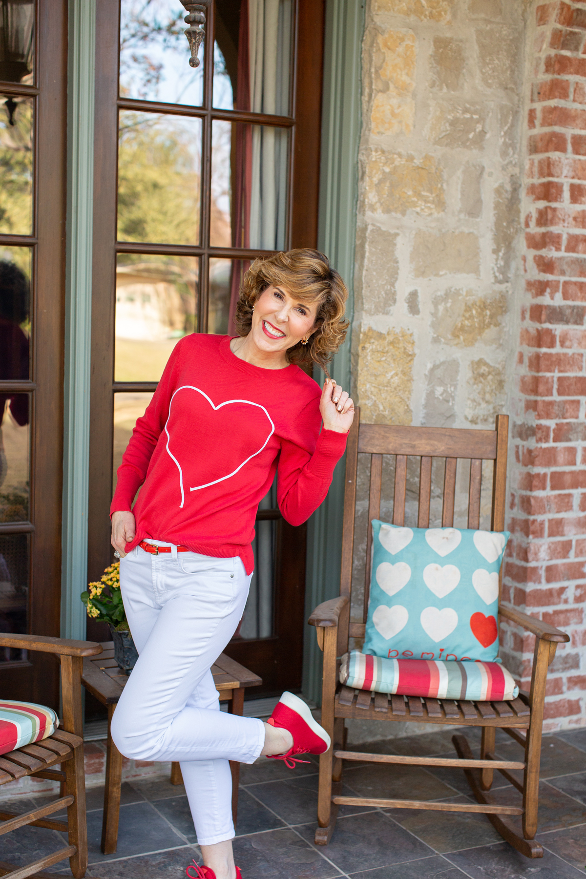woman in red heart sweater, white jeans, and red sneakers on a porch