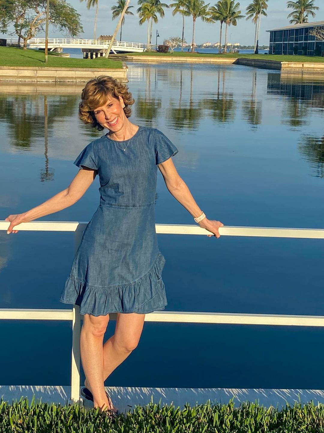 woman in blue dress standing against a white railing in front of water