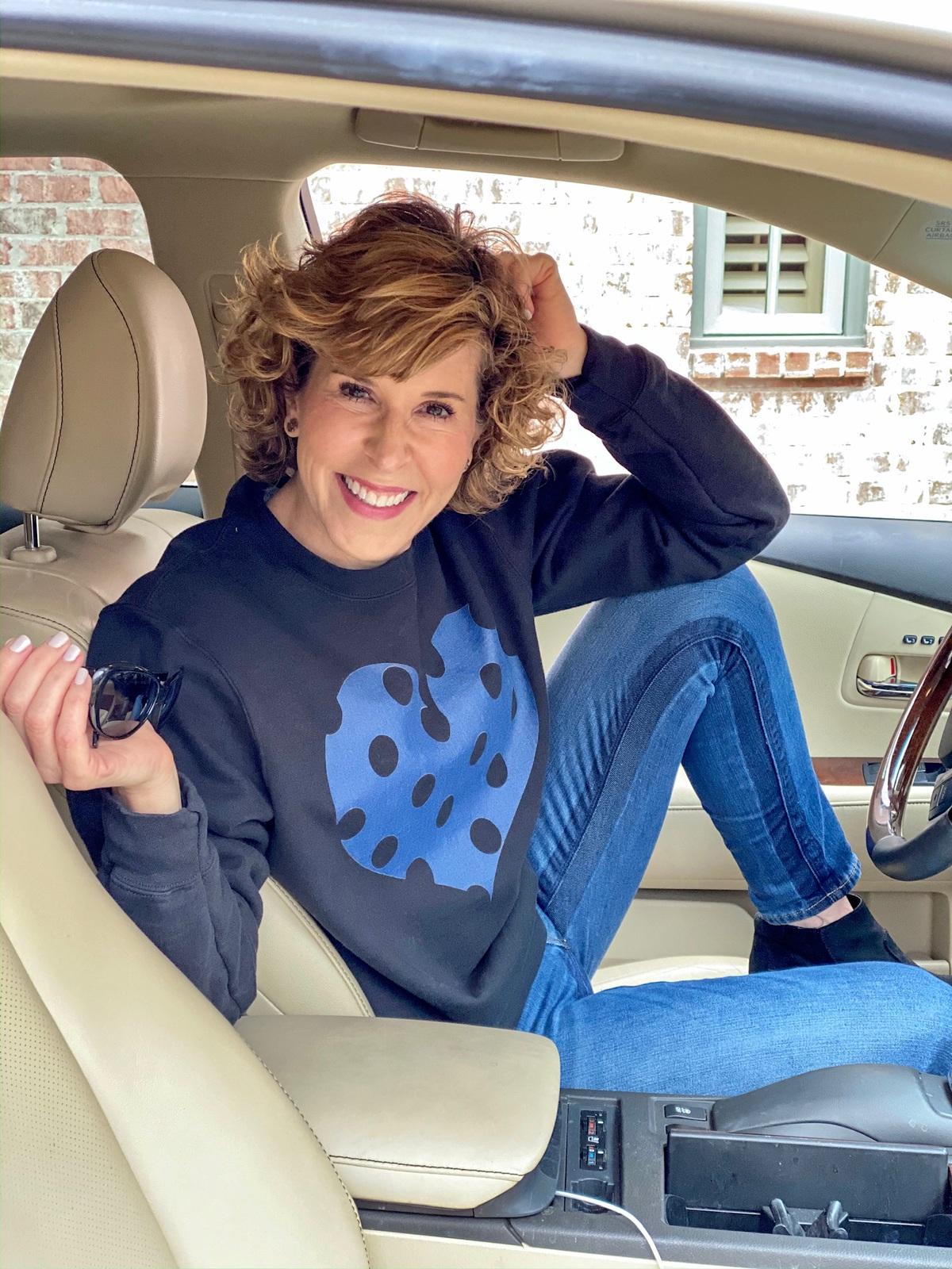 woman sitting in car with one leg up on her seat wearing black sweatshirt with blue polka dot heart sweatshirt