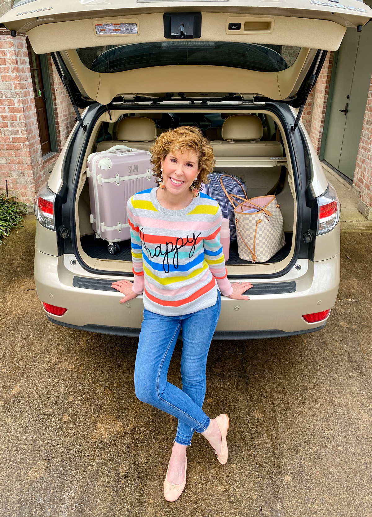 "woman wearing colorful striped ""happy"" sweater sitting on the trunk of her car"