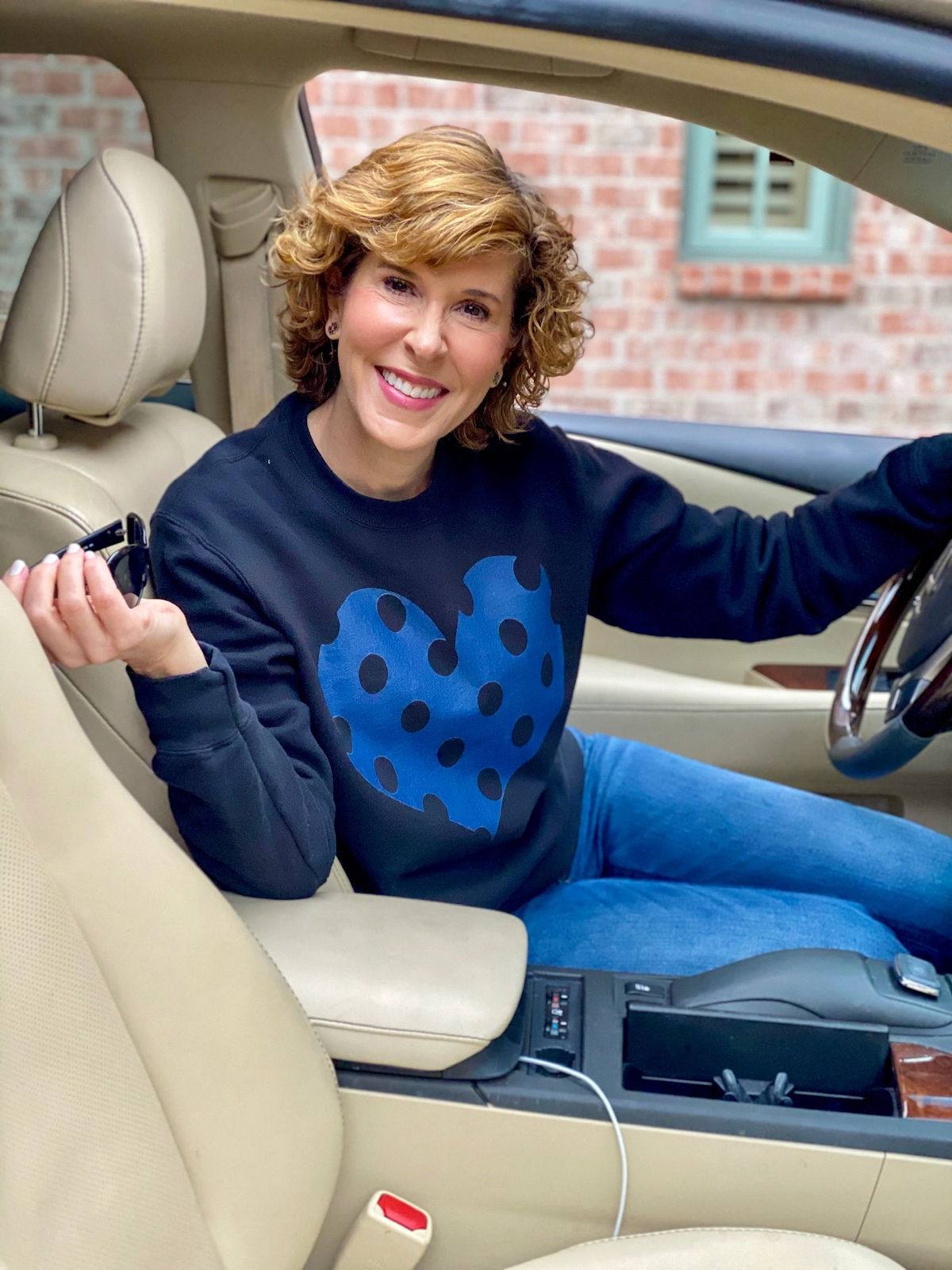 woman sitting in car wearing black sweatshirt with blue polka dot heart