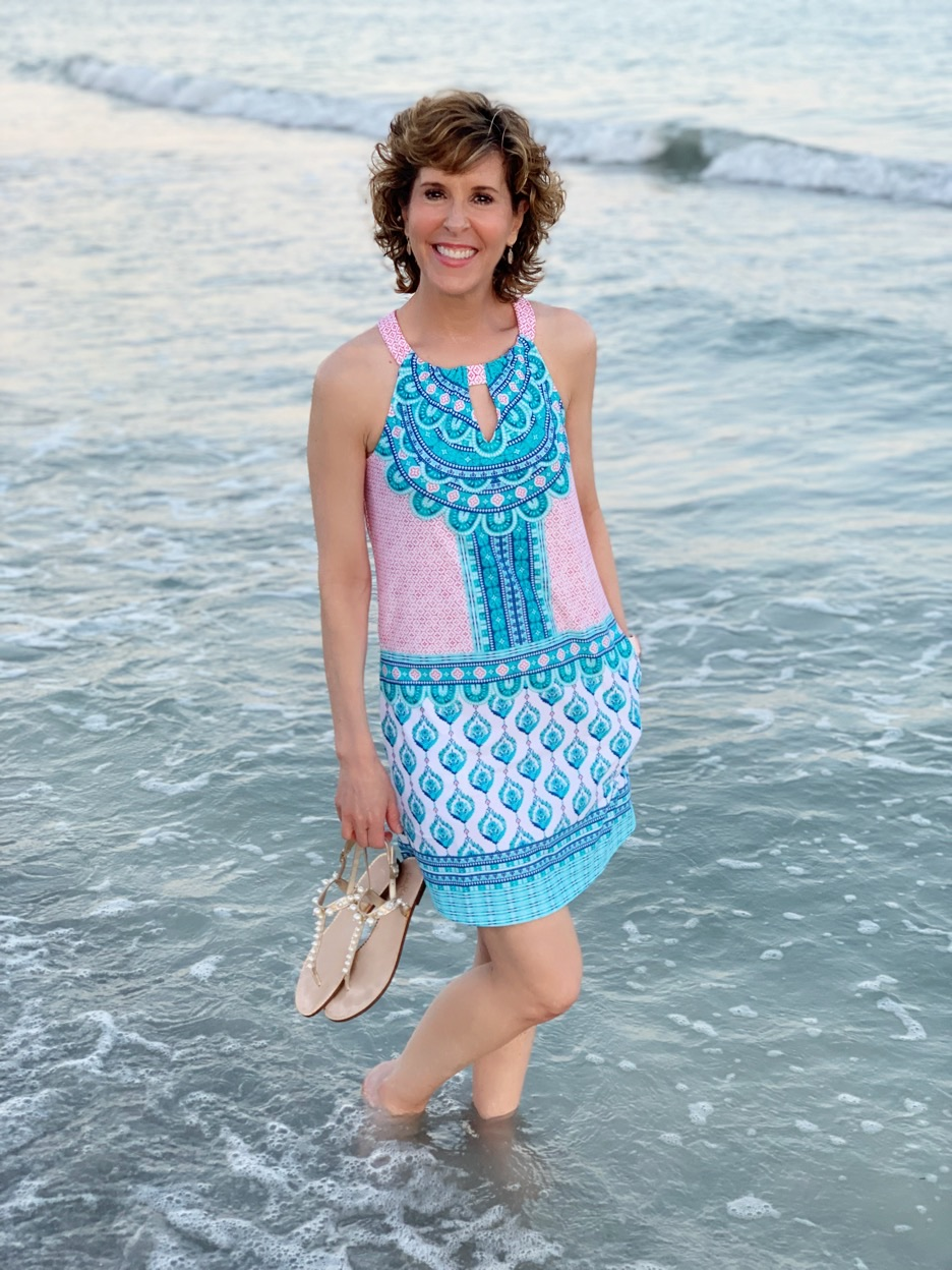woman wearing colorful dress standing in the surf