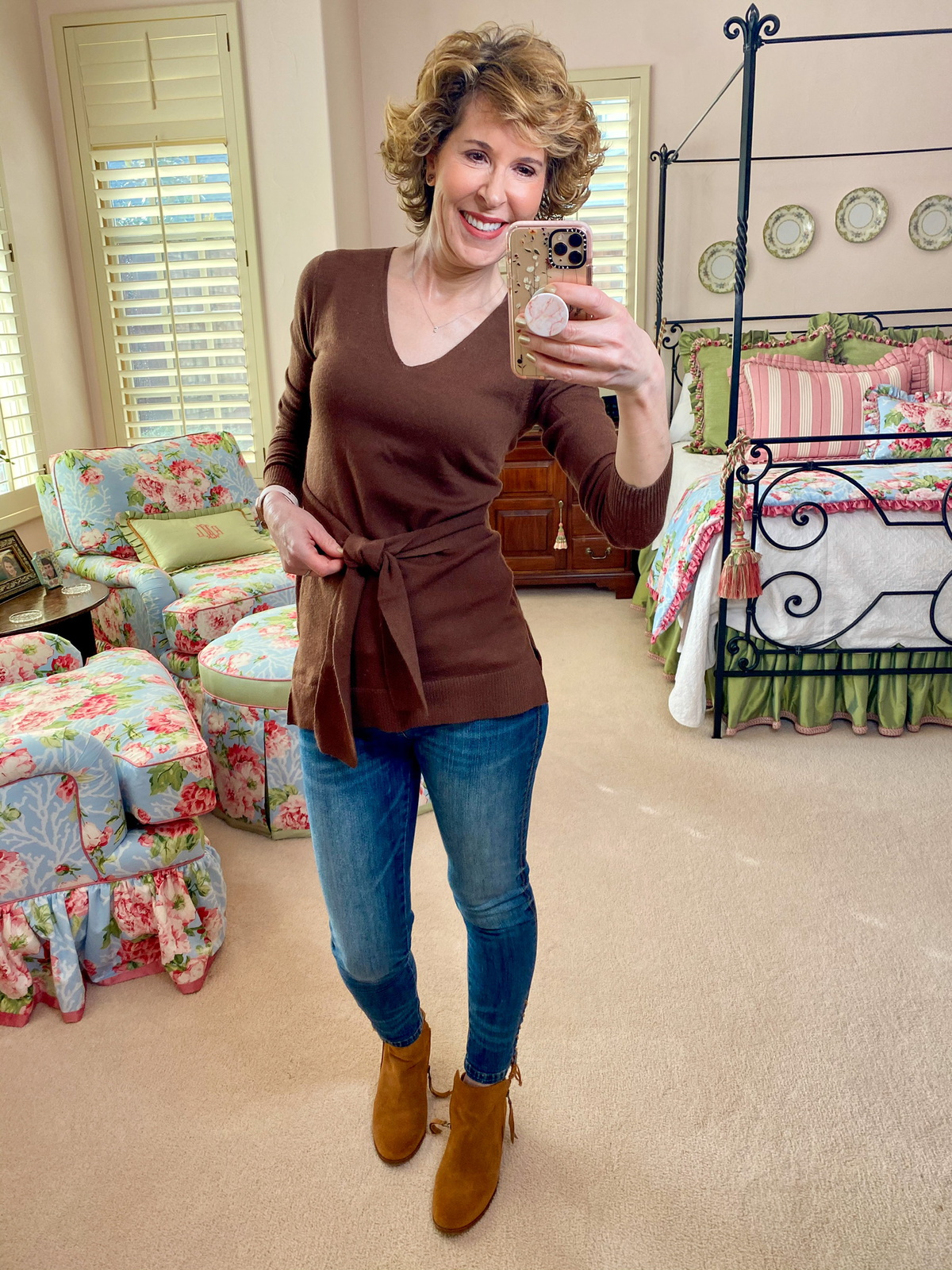 mirror selfie of woman in brown sweater and jeans with brown booties