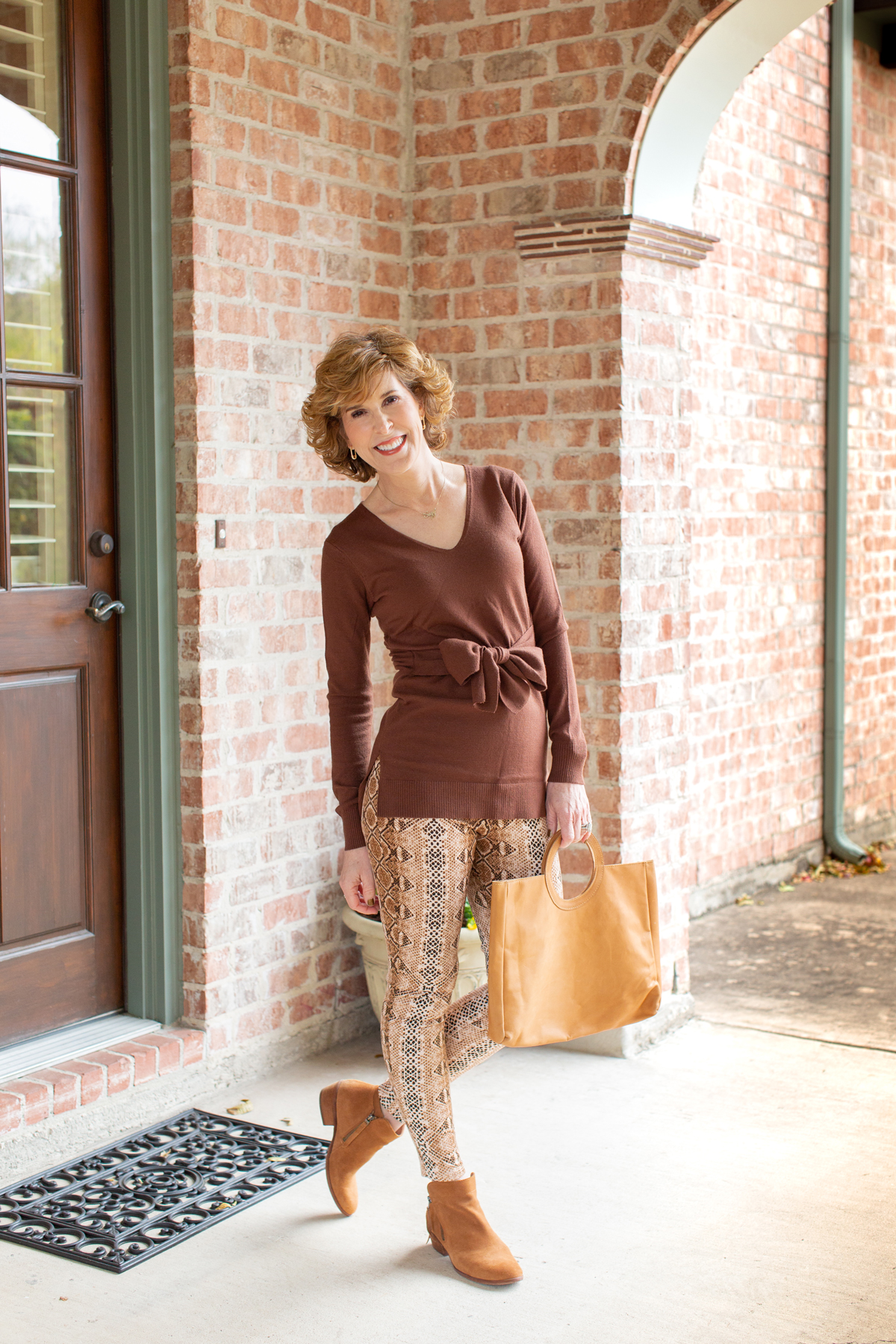 woman in brown tie waist sweater and snake print leggings outside a house