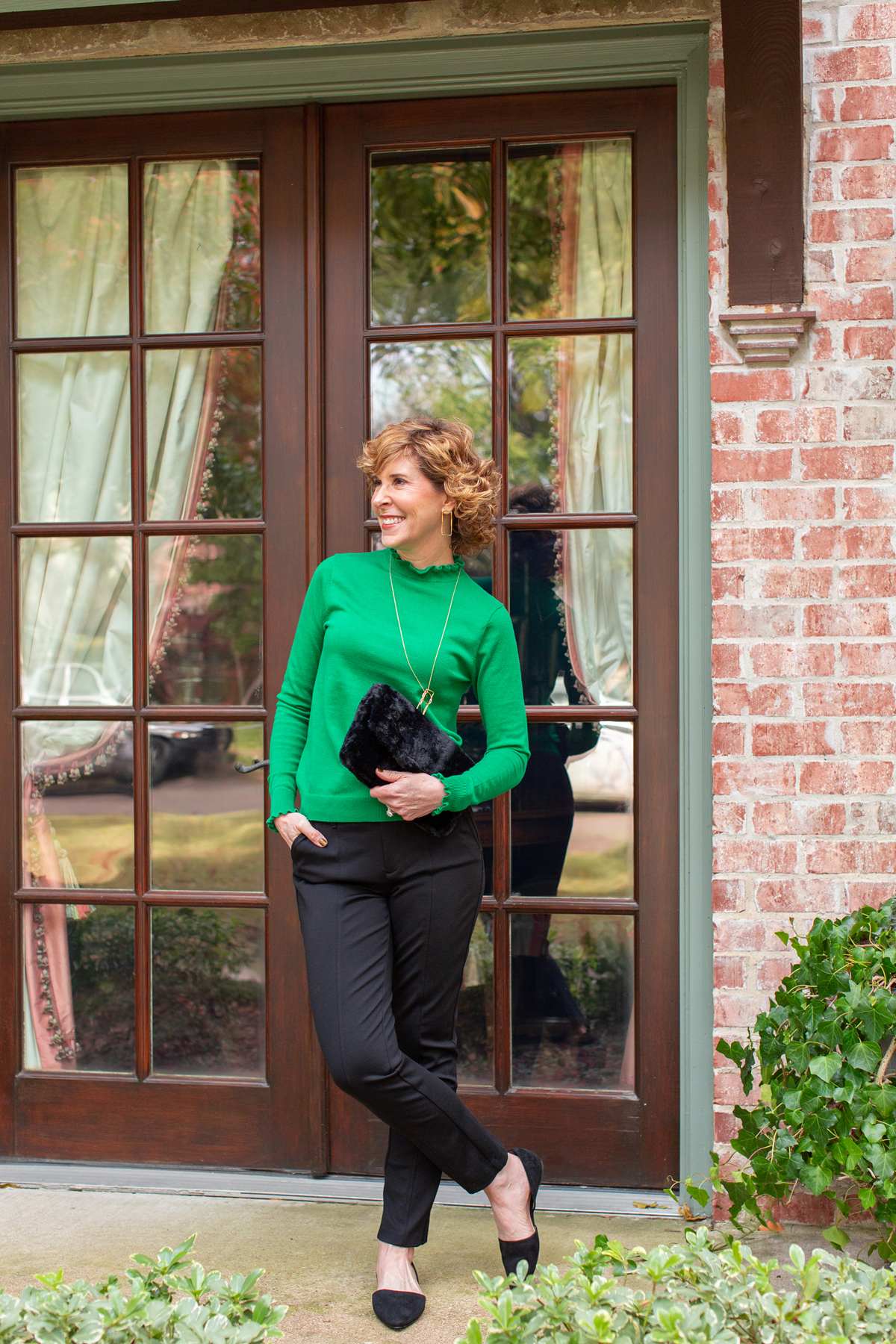 woman in green sweater and black pants standing outside a house