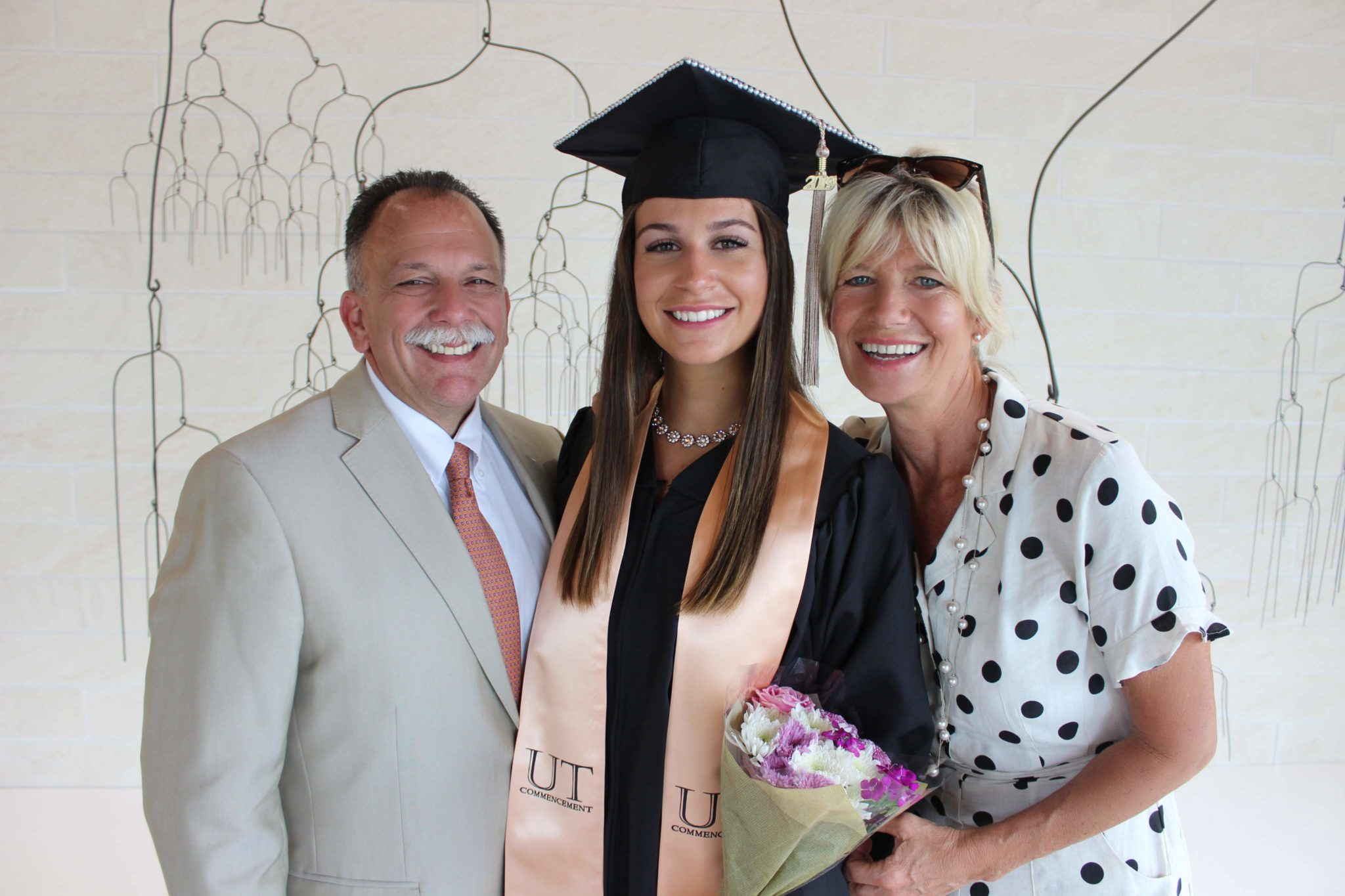 graduation photo of woman in cap and gown with parents on either side
