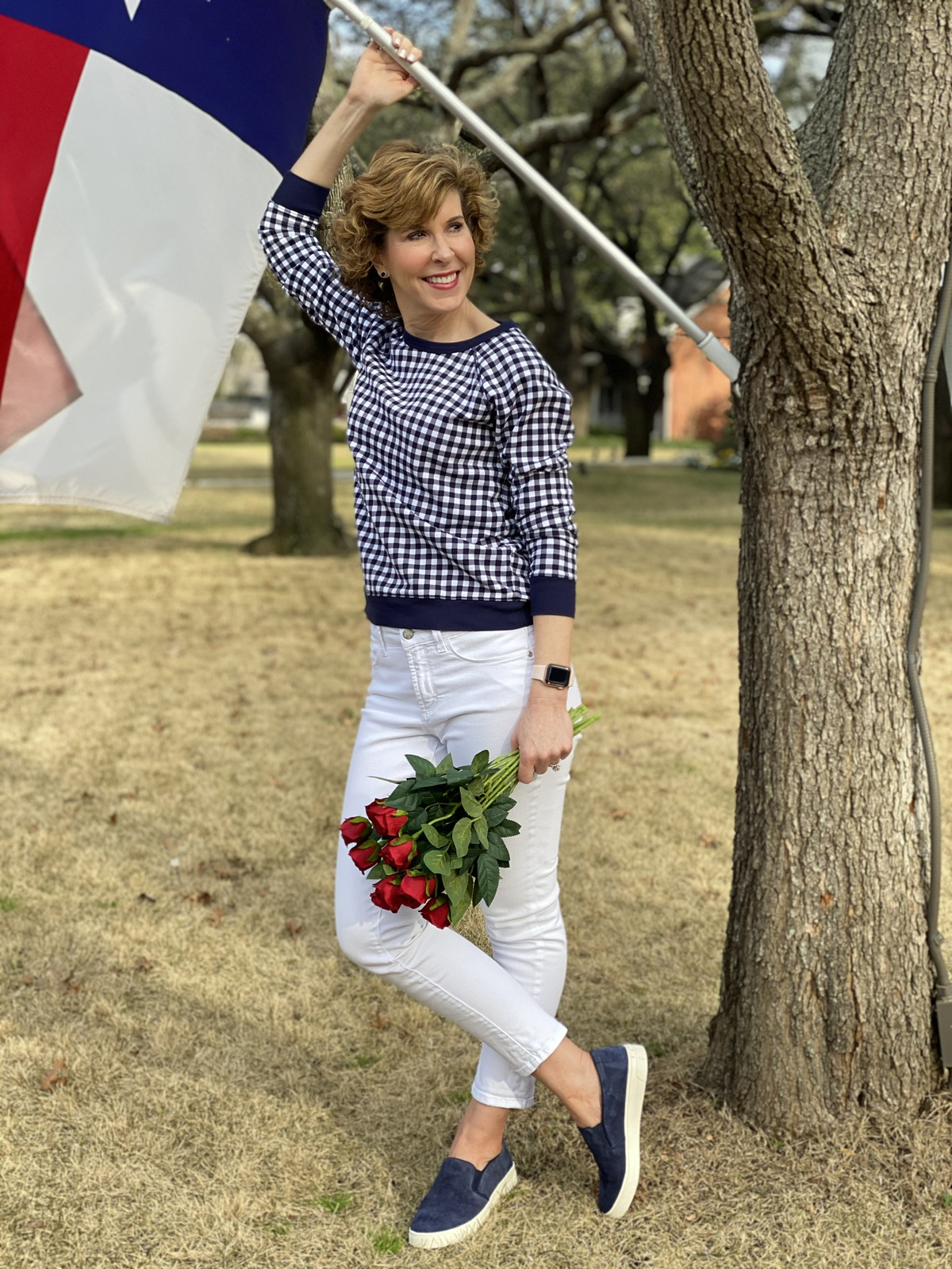 woman over 50 wearing navy and white gingham sweatshirt and white jeans standing by a texas flag and holding red roses